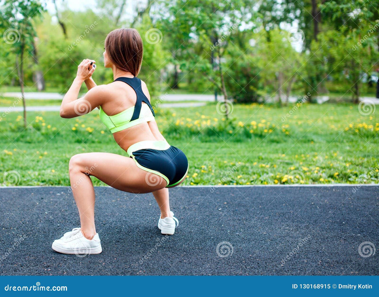Menina dos esportes no sportswear que squatting no parque do verão