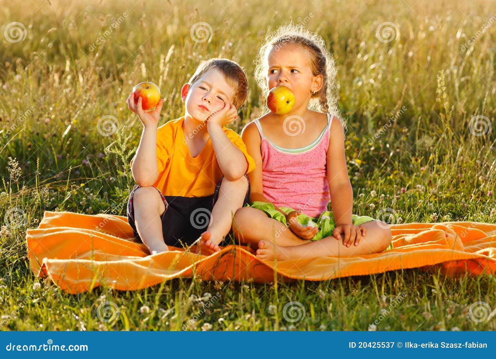 Menina e menino que comem a maçã