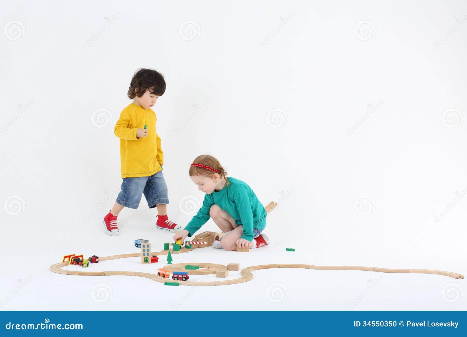 A menina e o menino entusiásticos pequenos jogam com estrada de ferro de madeira