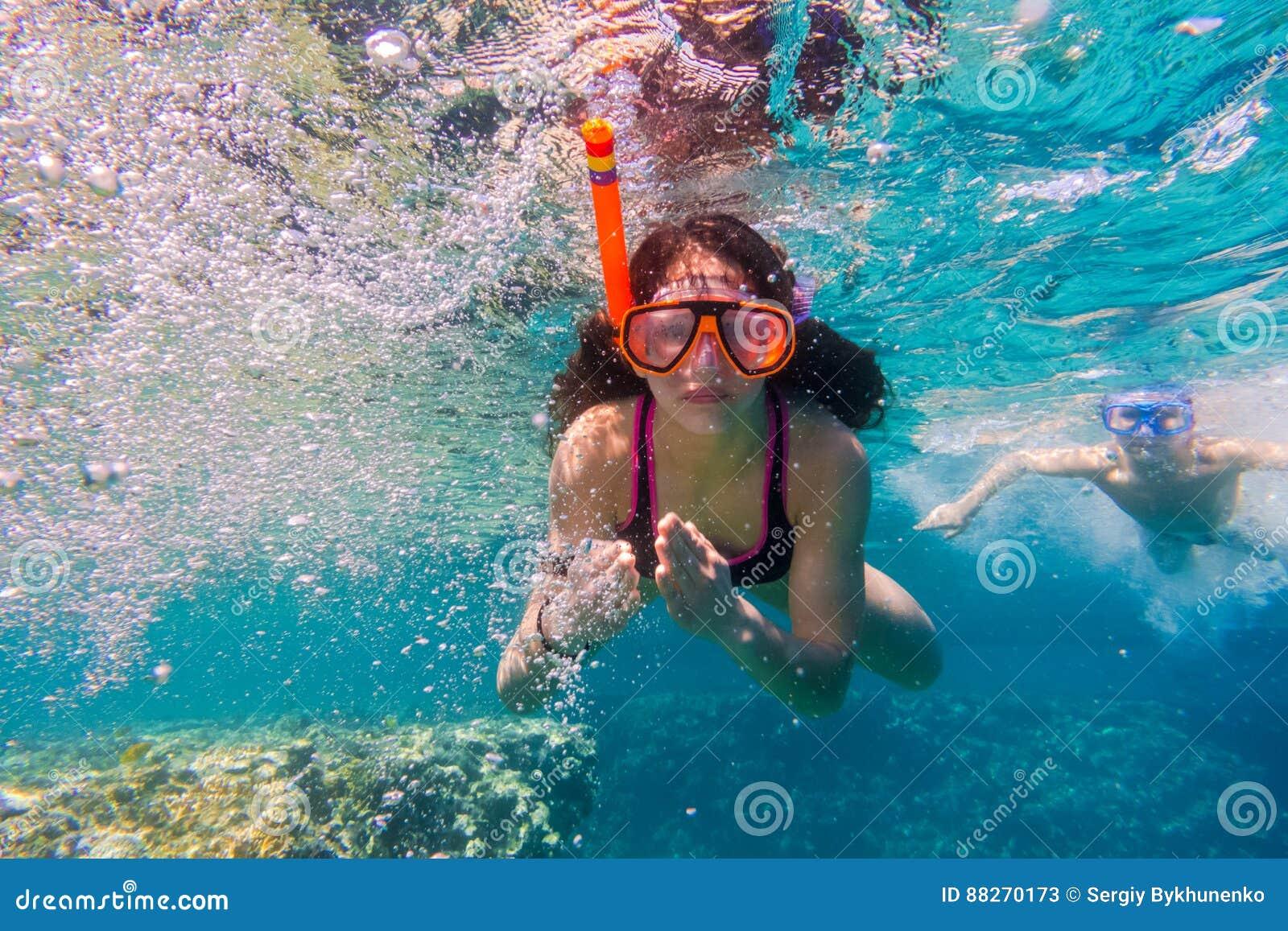 A menina e o menino na máscara da natação mergulham no Mar Vermelho perto do recife de corais