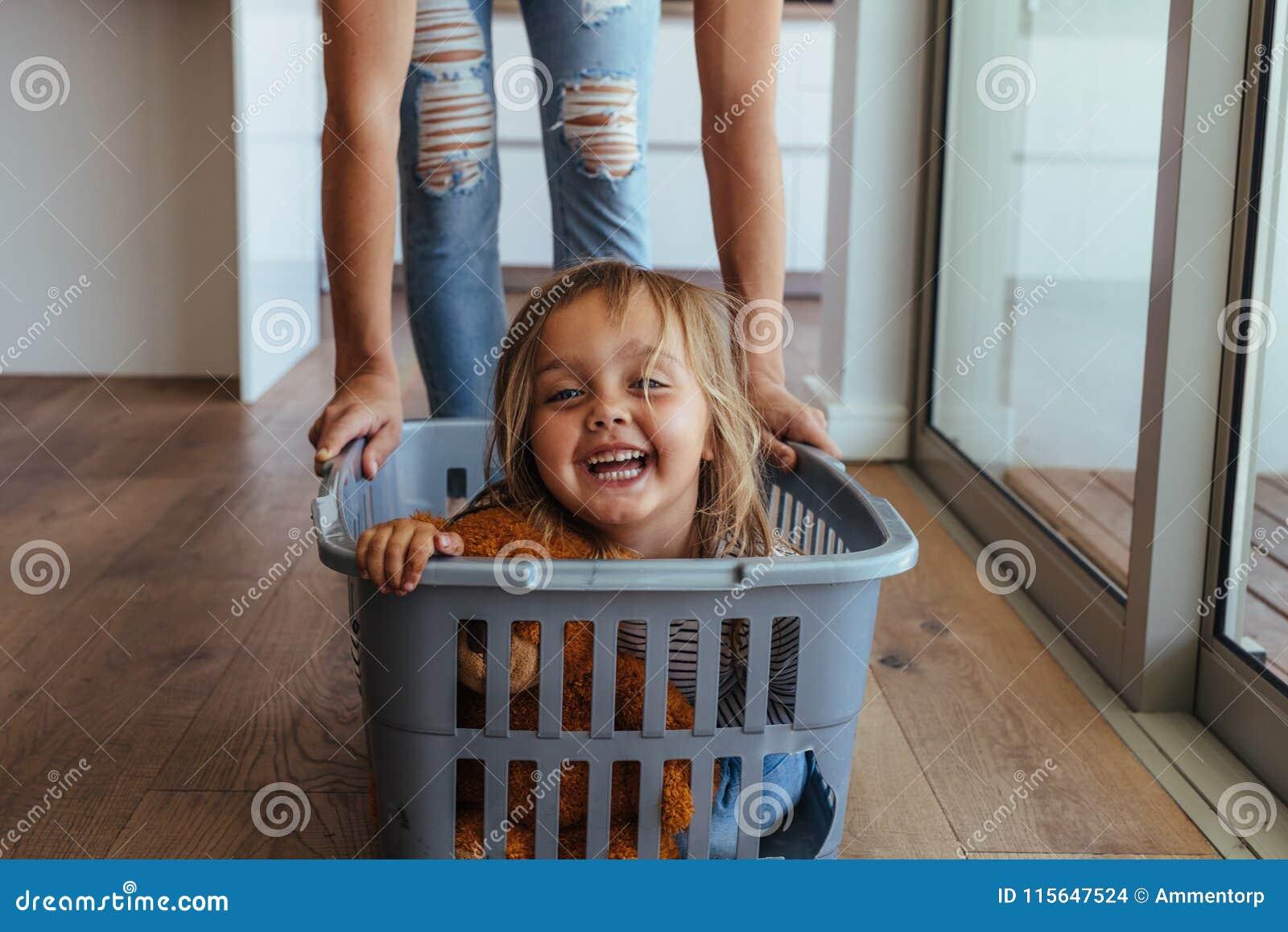 Menina e sua mãe que têm o divertimento que faz a lavanderia