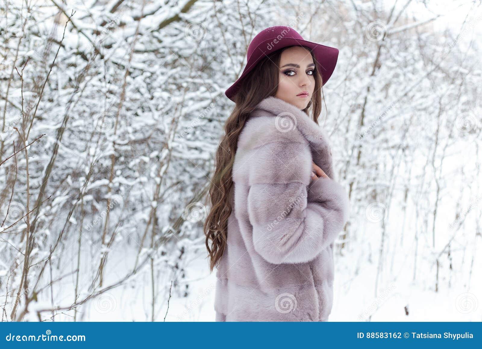 Menina elegante bonito bonita em um casaco de pele e em um chapéu que anda na manhã gelado brilhante da floresta do inverno