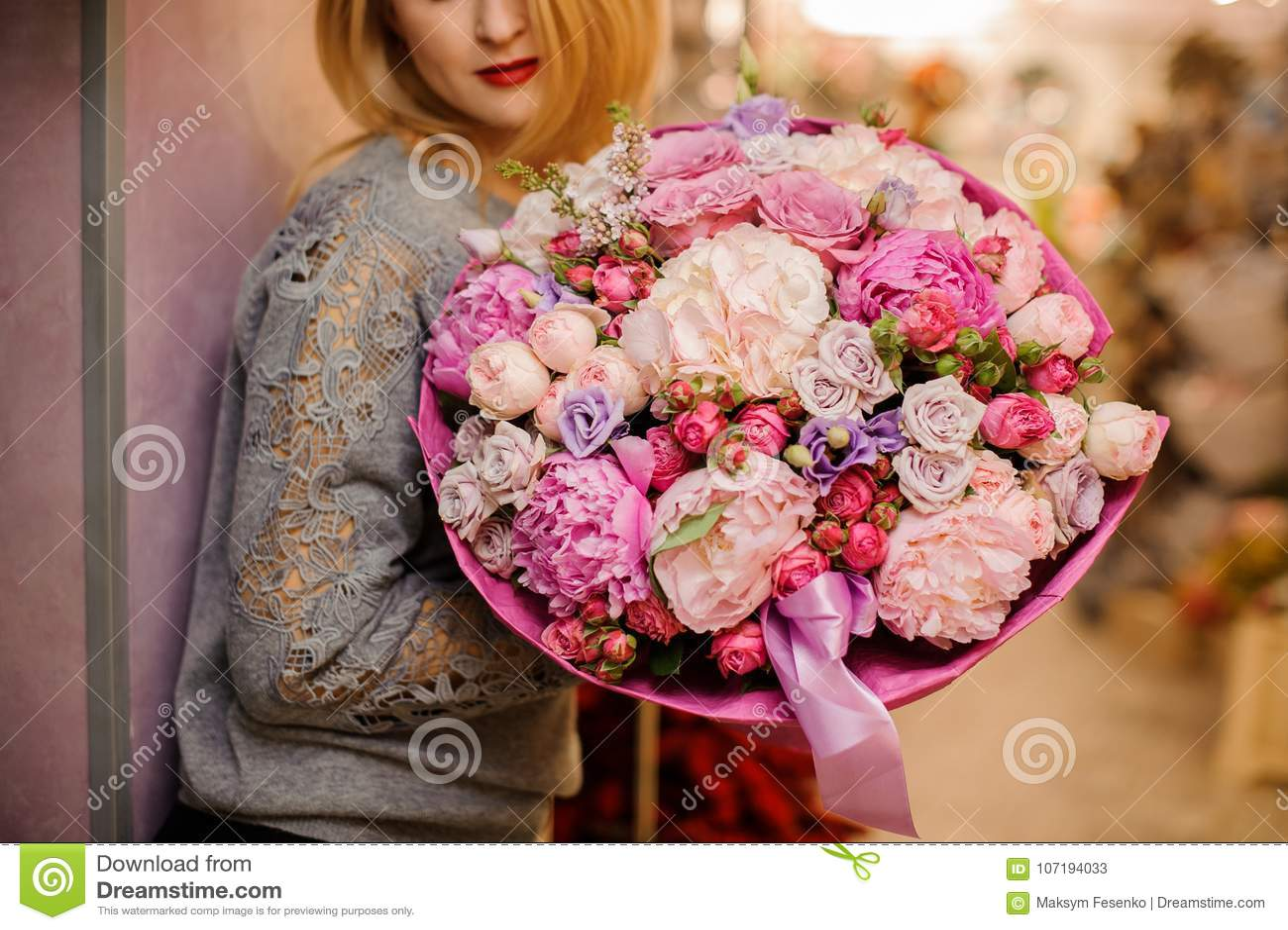 A menina elegante sorri posses um ramalhete enorme de flores cor-de-rosa e roxas diferentes