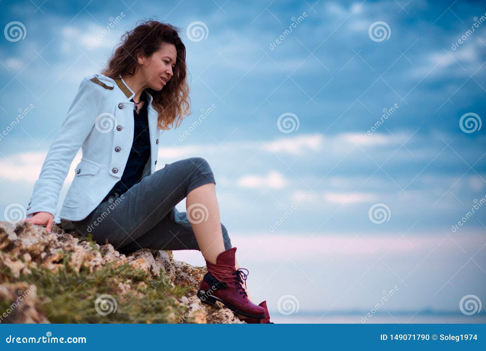 A menina elegante vestida no revestimento branco e na cal?as larga que levantam no fundo do c?u do por do sol, senta-se na pedra