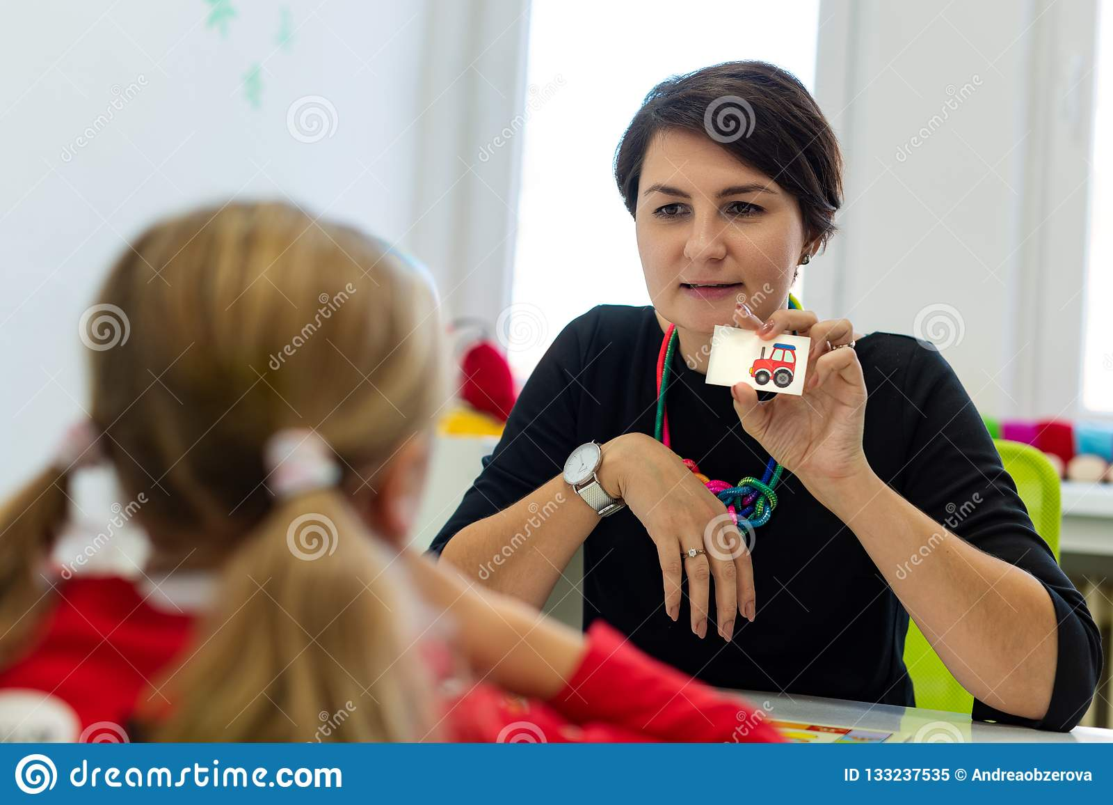Menina elementar da idade na sessão de terapia ocupacional da criança que faz exercícios brincalhão com seu terapeuta