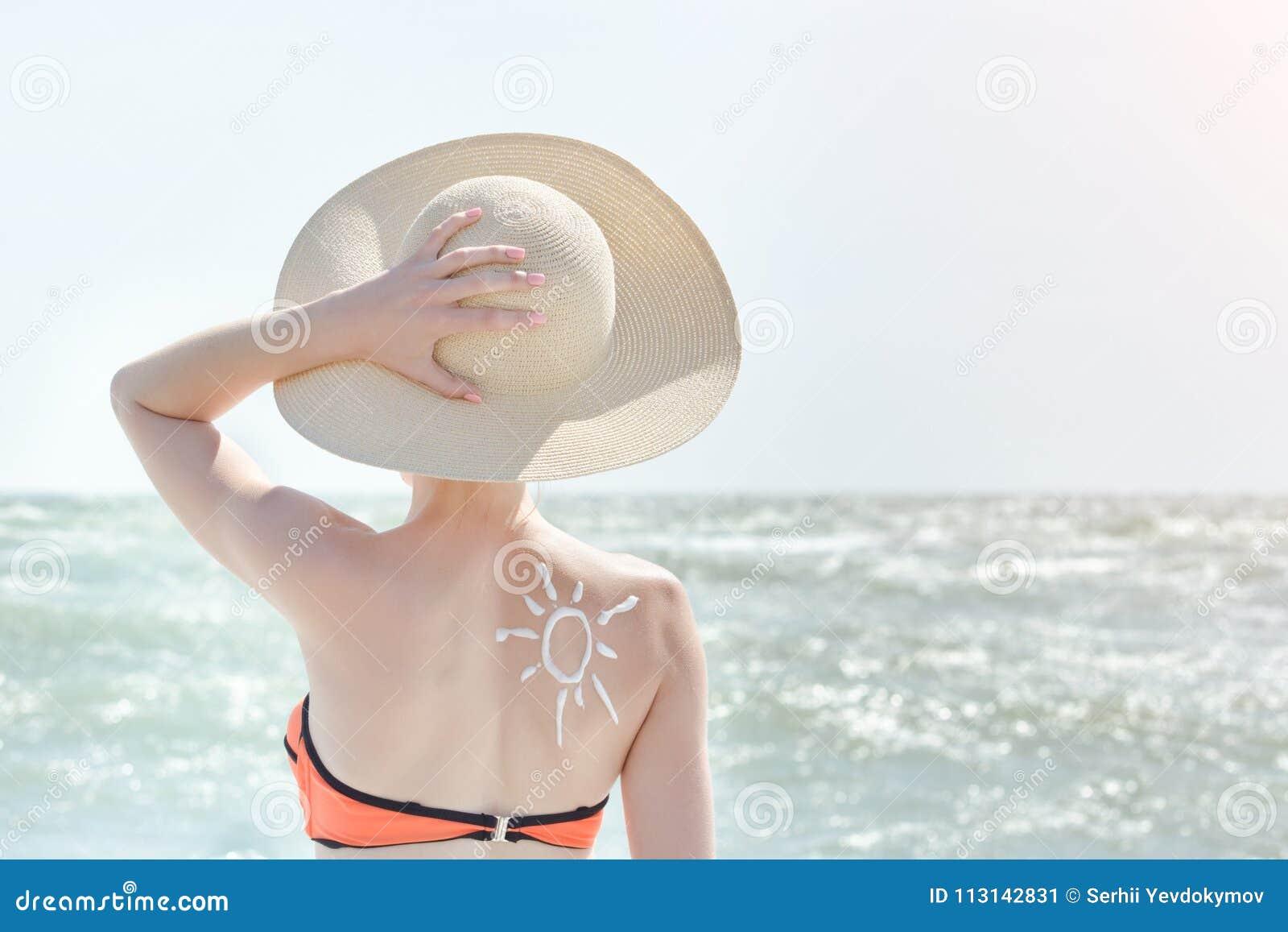 Menina em um chapéu contra o mar Na parte traseira é o sol pintado