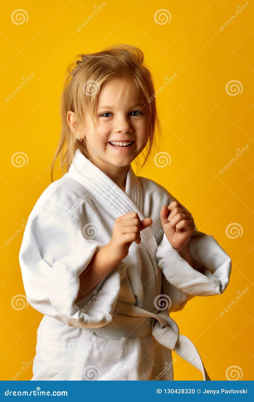 A menina em um fundo amarelo com correia branca está batendo o assistente