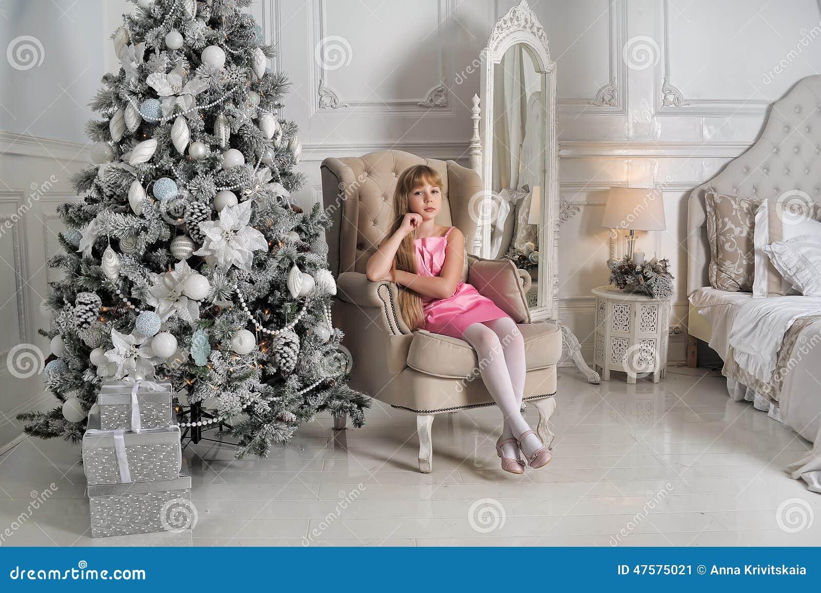 Menina em um pálido - vestido cor-de-rosa que senta-se em uma cadeira na árvore de Natal