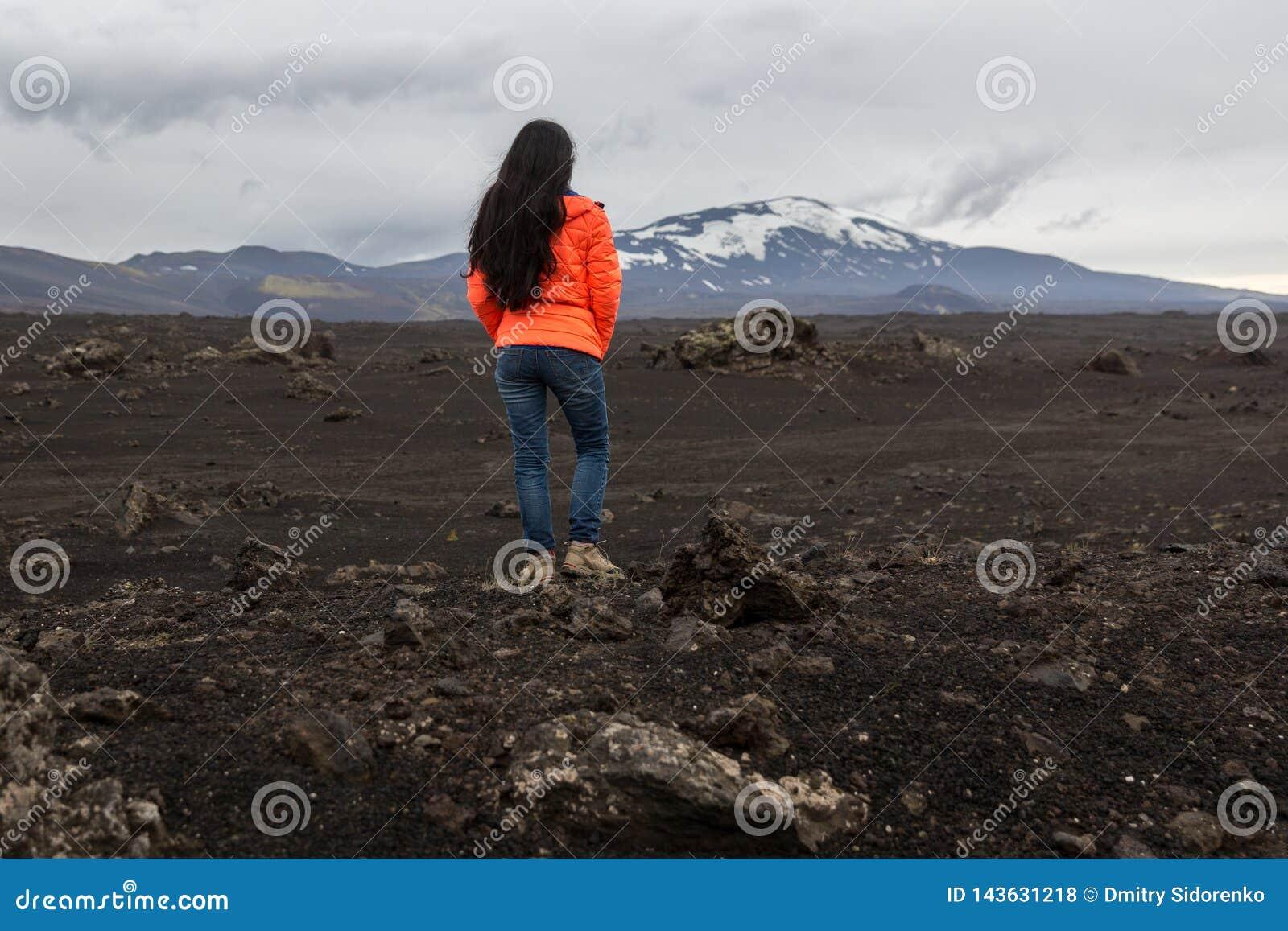 A menina em um revestimento alaranjado está em uma pedra