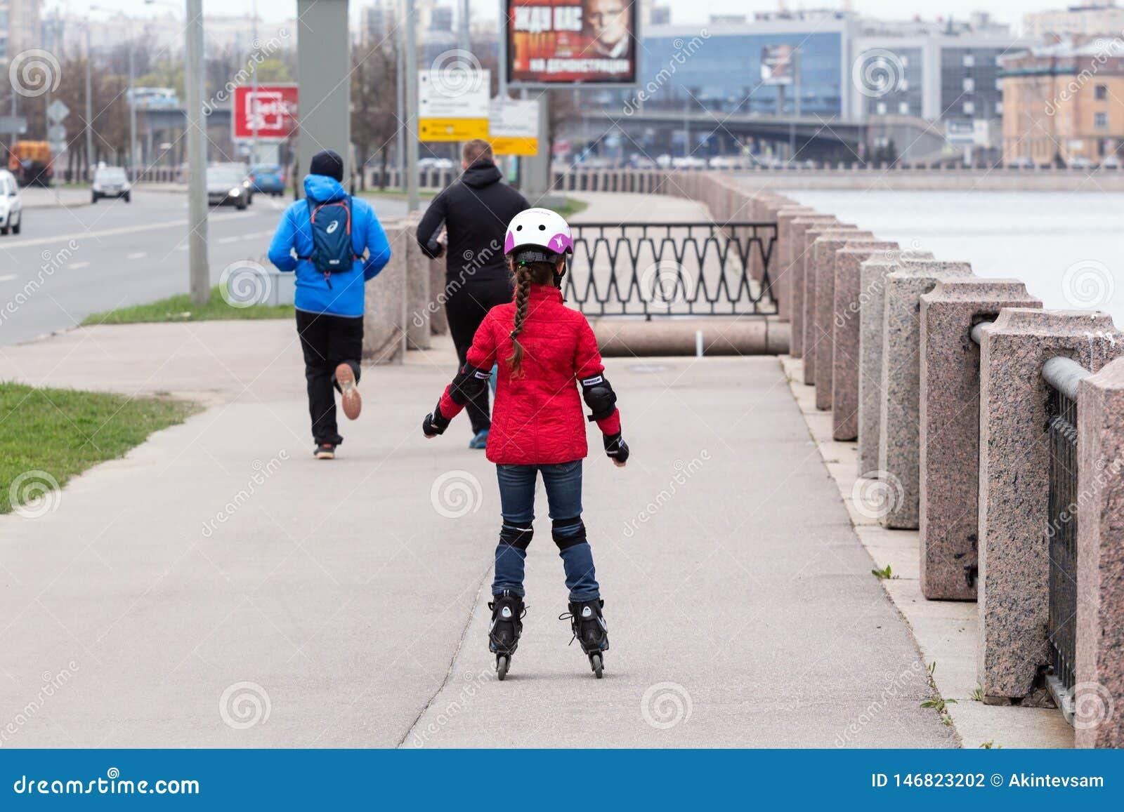 Menina em um revestimento vermelho e na calças de ganga que rollerblading