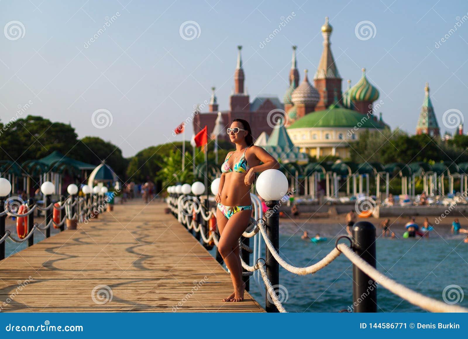Menina em um roupa de banho no cais no fundo do hotel menina que levanta no cais de madeira na praia, contra o contexto