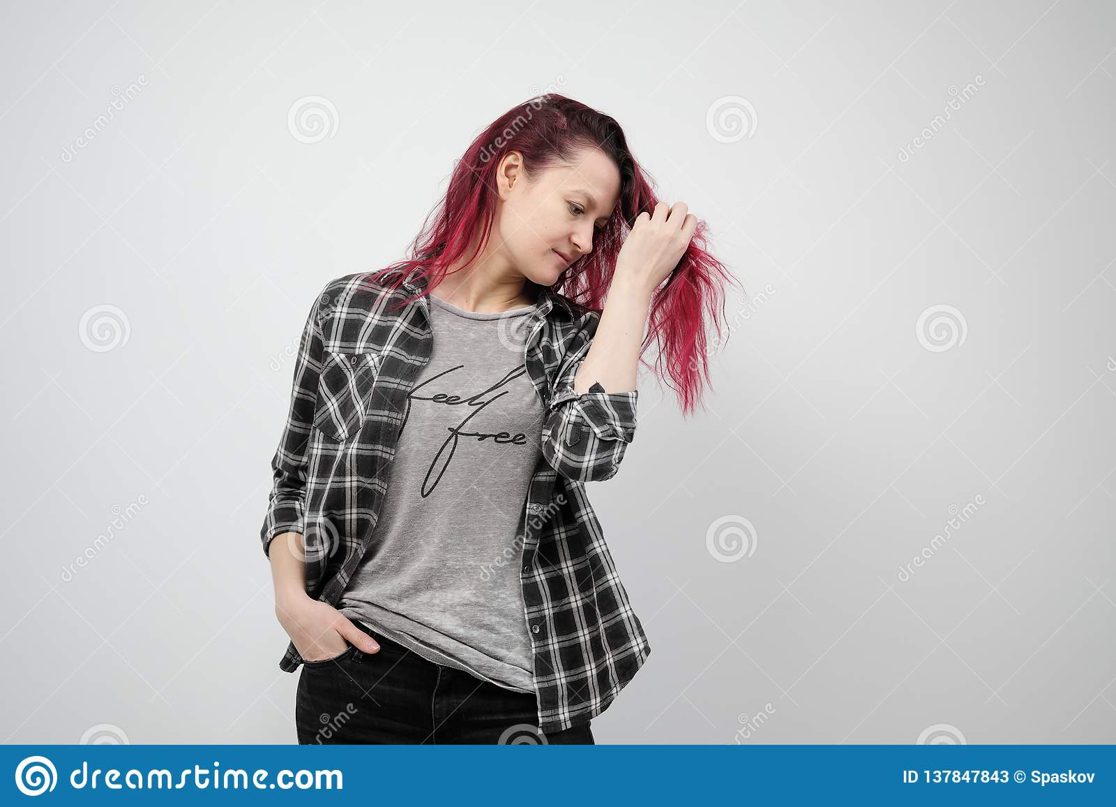 A menina em uma camisa cinzenta da manta em um fundo branco com cabelo vermelho tingido