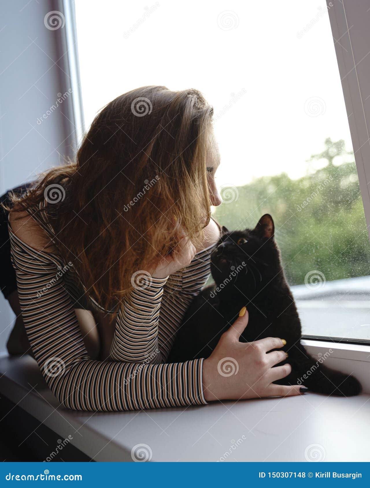 A menina em uma saia e um gato estão sentando-se na janela na noite da rua