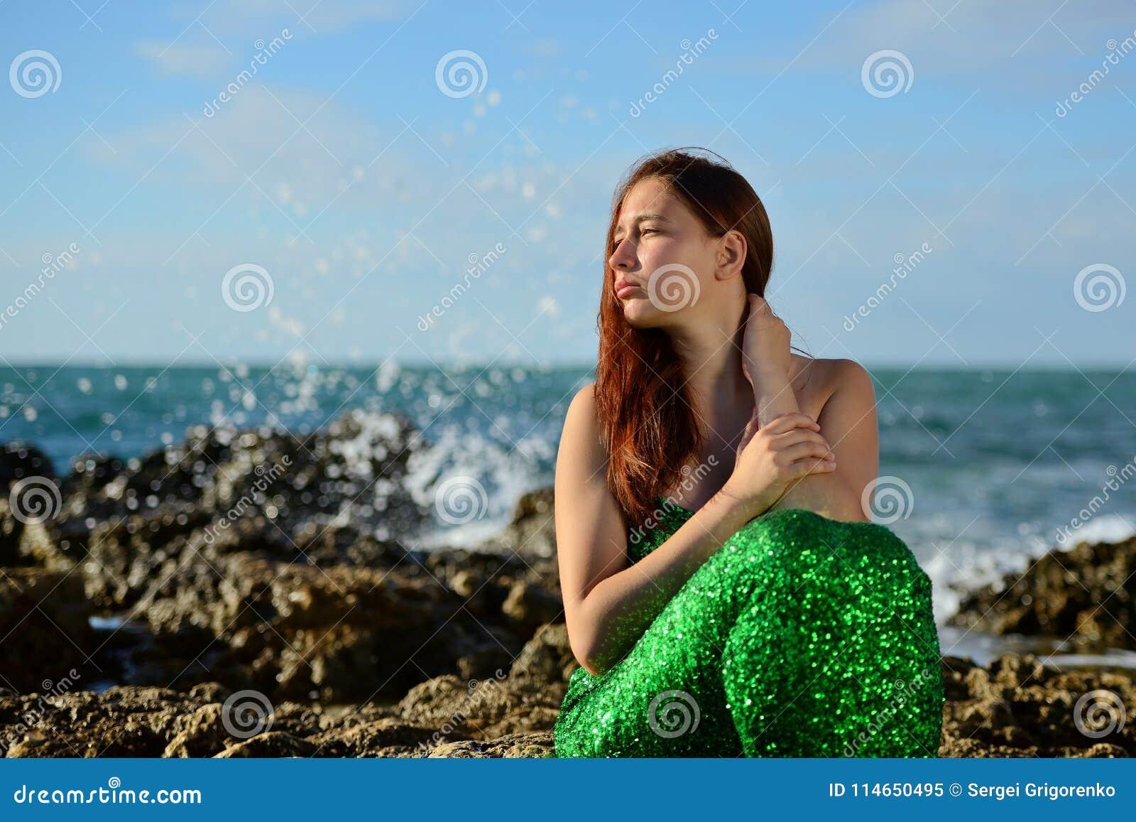 Menina em uma sereia brilhante do traje que senta-se no litoral no fundo do pulverizador e dos olhares no por do sol
