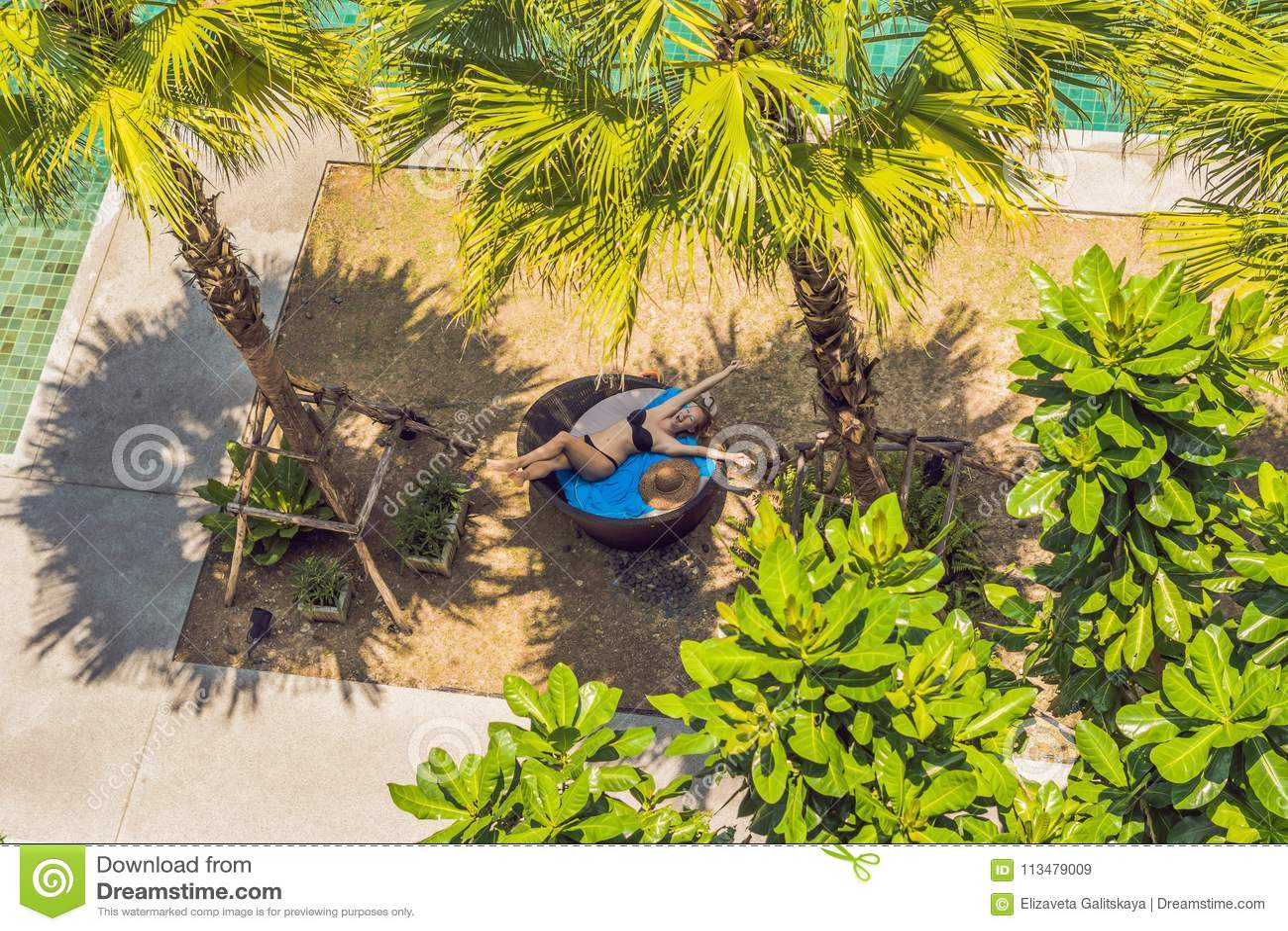 Menina em vadios do sol entre palmeiras perto da piscina