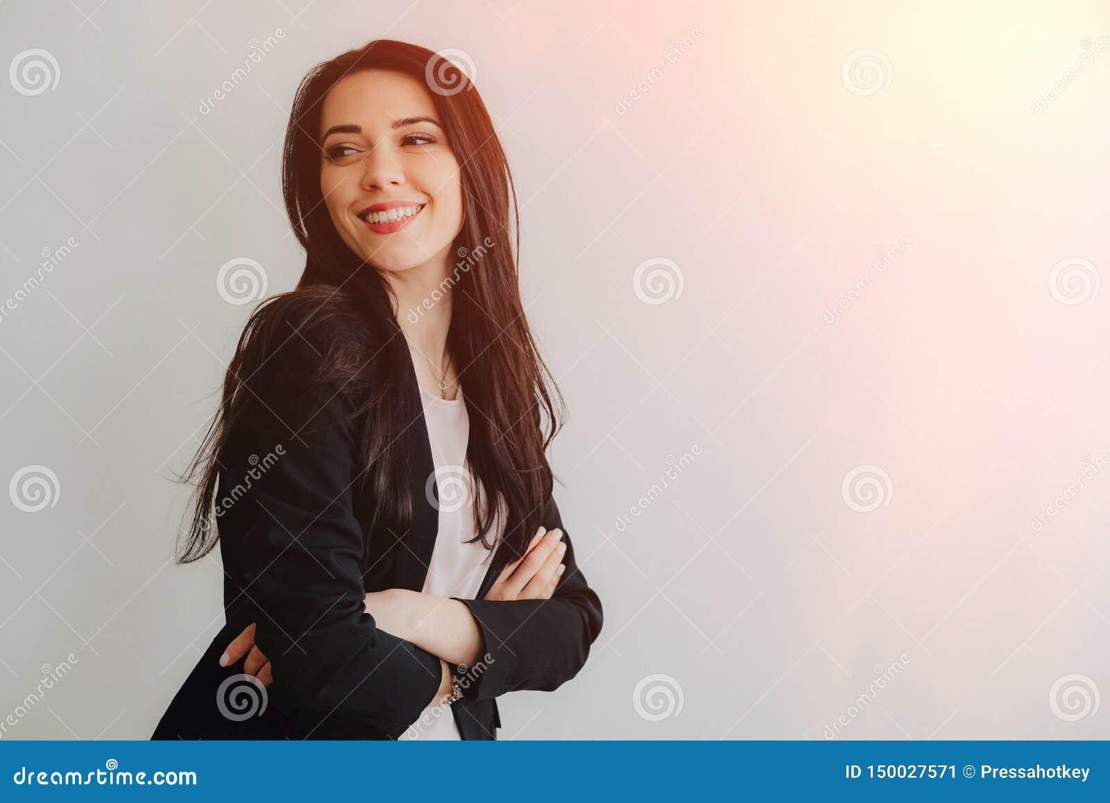 Menina emocional atrativa nova na roupa do neg?cio-estilo em um fundo branco liso em um escrit?rio ou em uma audi?ncia