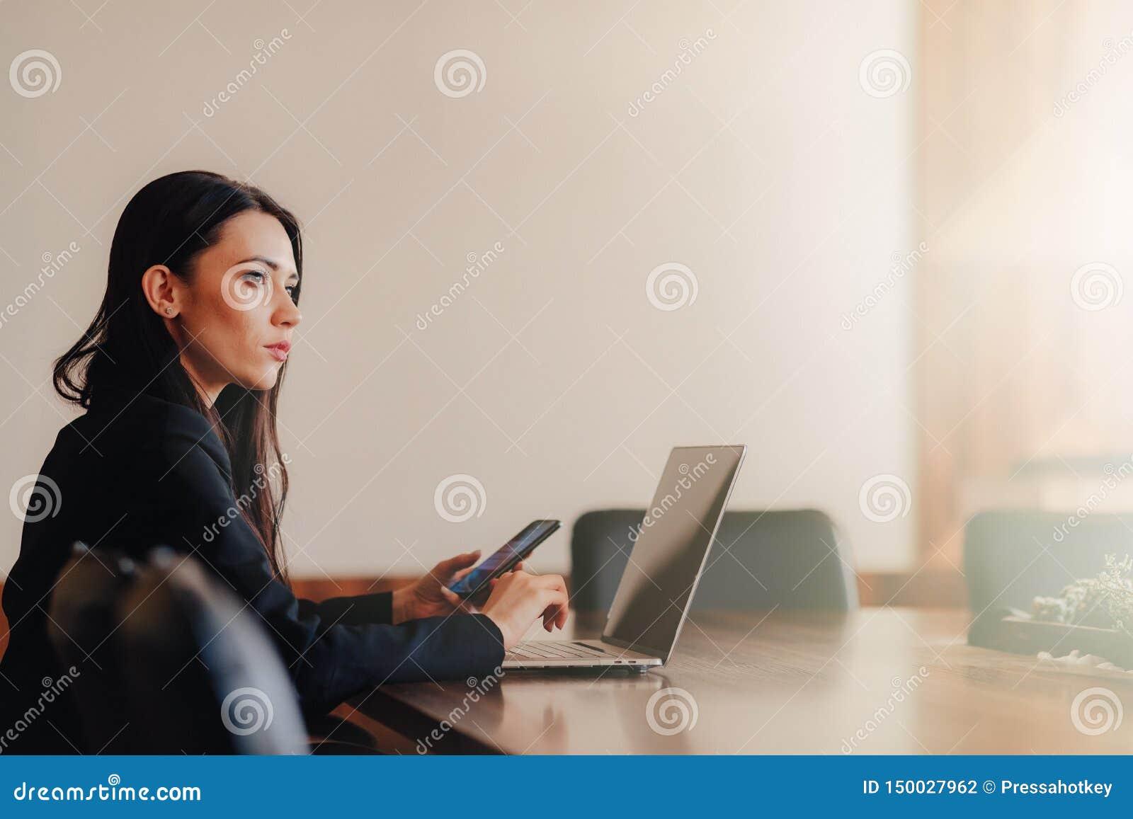 Menina emocional atrativa nova na roupa do neg?cio-estilo que senta-se em uma mesa em um port?til e em um telefone no escrit?rio