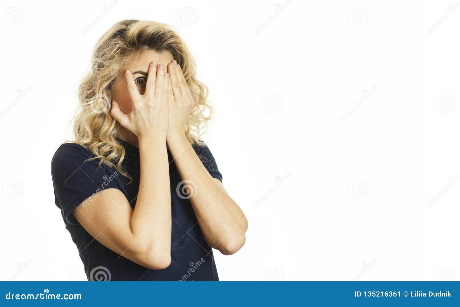 A menina emocional nova bonita fecha seus olhos a um fundo branco isolado Não queira ver