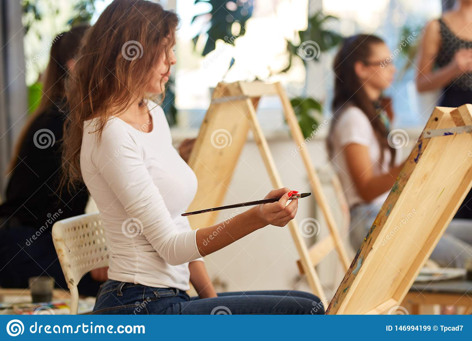 A menina encantador nova com o cabelo encaracolado marrom vestido na blusa branca pinta uma imagem na arma??o na escola de tirage