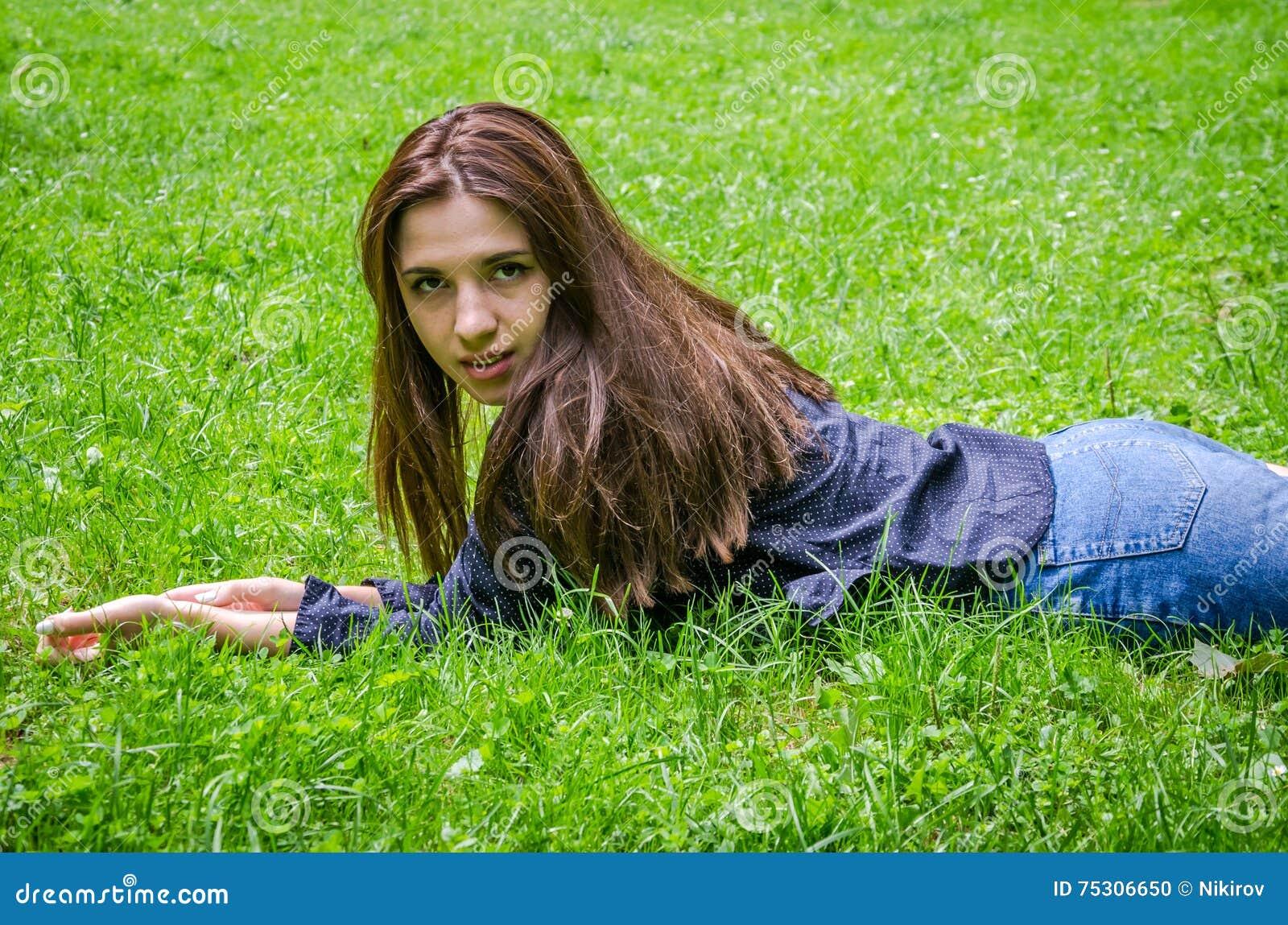 Menina encantador nova o adolescente com o cabelo longo que encontra-se para baixo e que descansa na grama verde ao andar no parq