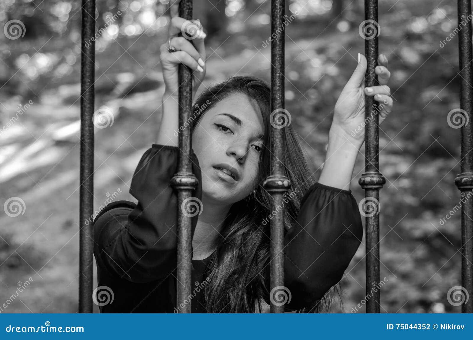 A menina encantador nova o adolescente com o cabelo longo que senta-se atrás das barras no prisioneiro da prisão em uma cadeia me