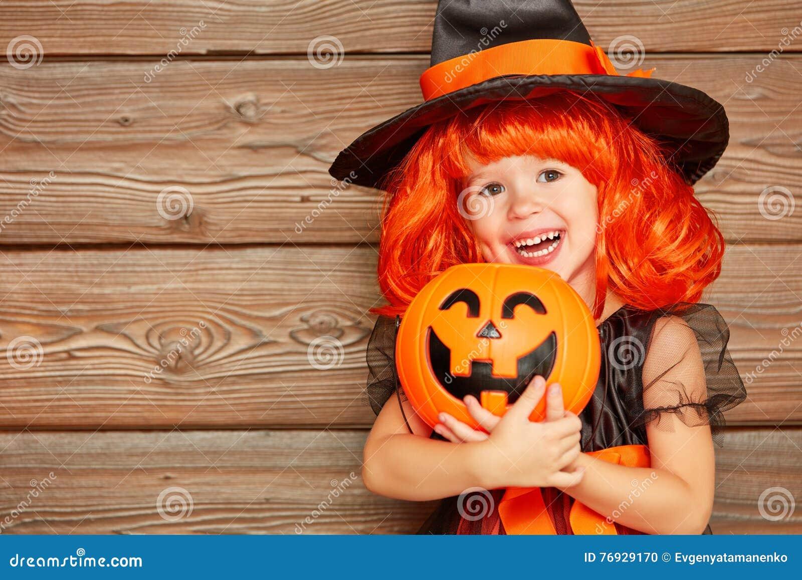 Menina engraçada da criança no traje da bruxa para Dia das Bruxas com abóbora Ja