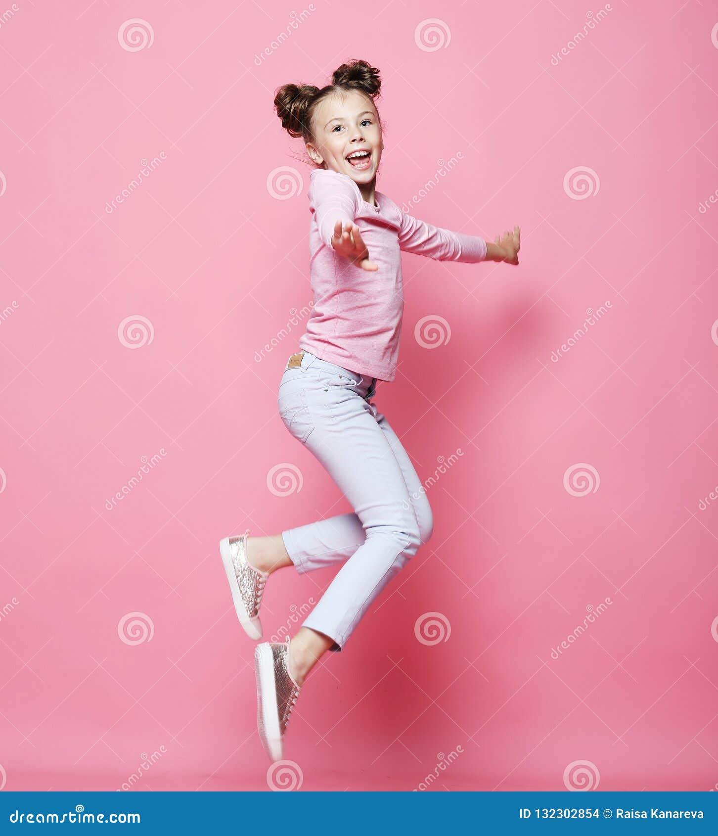 A menina engraçada da criança vestiu o salto ocasional no fundo cor-de-rosa