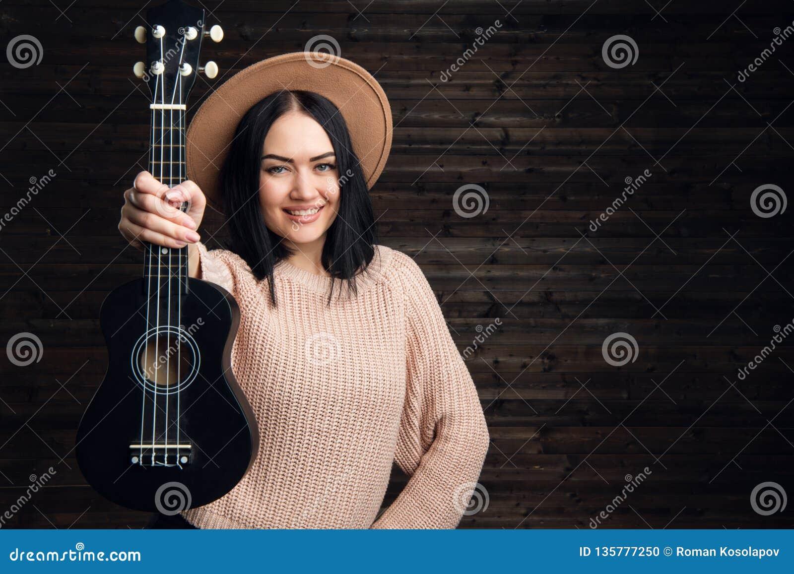 Menina engraçada nova do moderno que tem o divertimento e que joga na guitarra pequena, no canto e na dança da uquelele chapéu ve