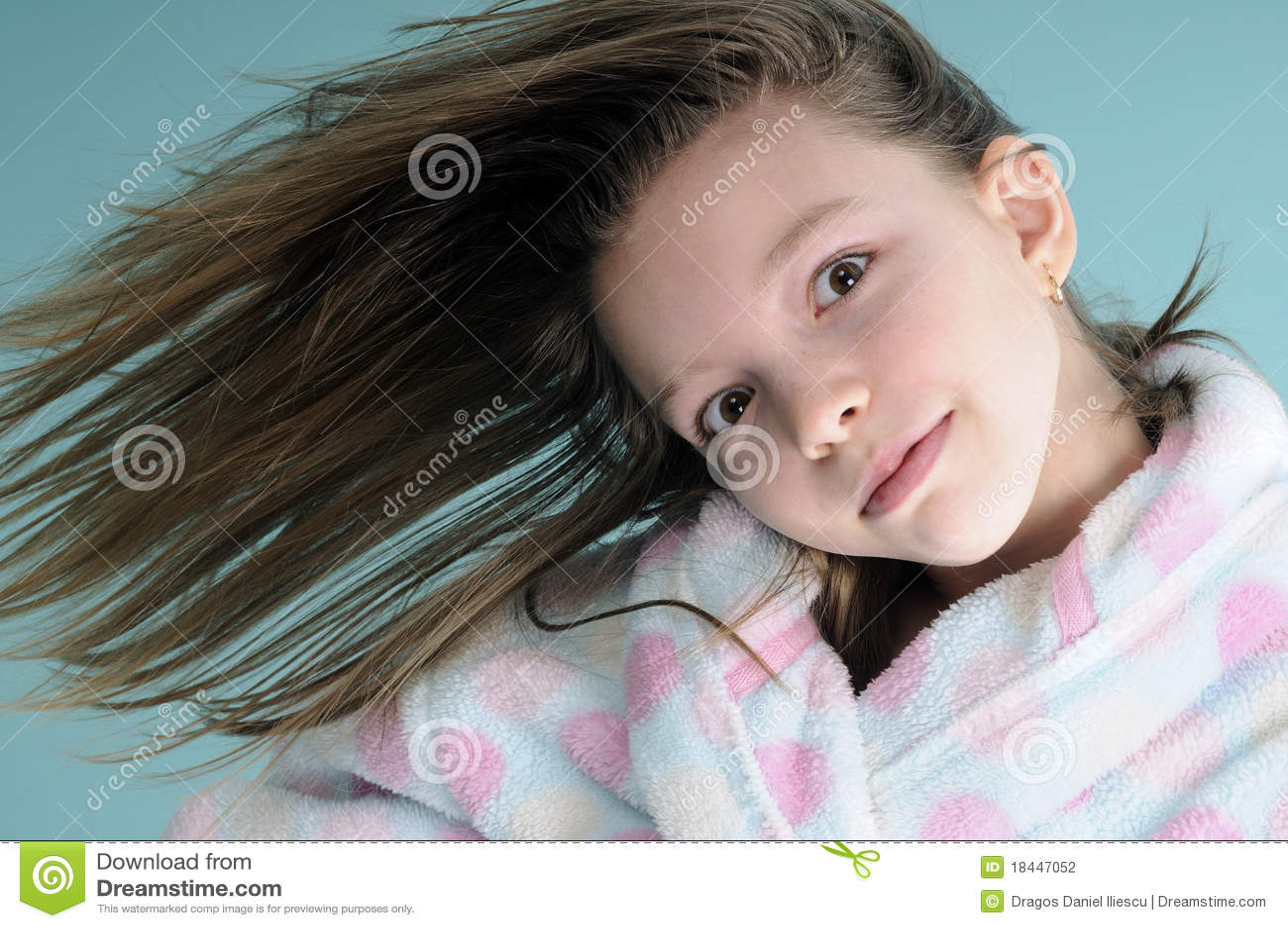 Menina engraçada que mostra a ondulação do cabelo