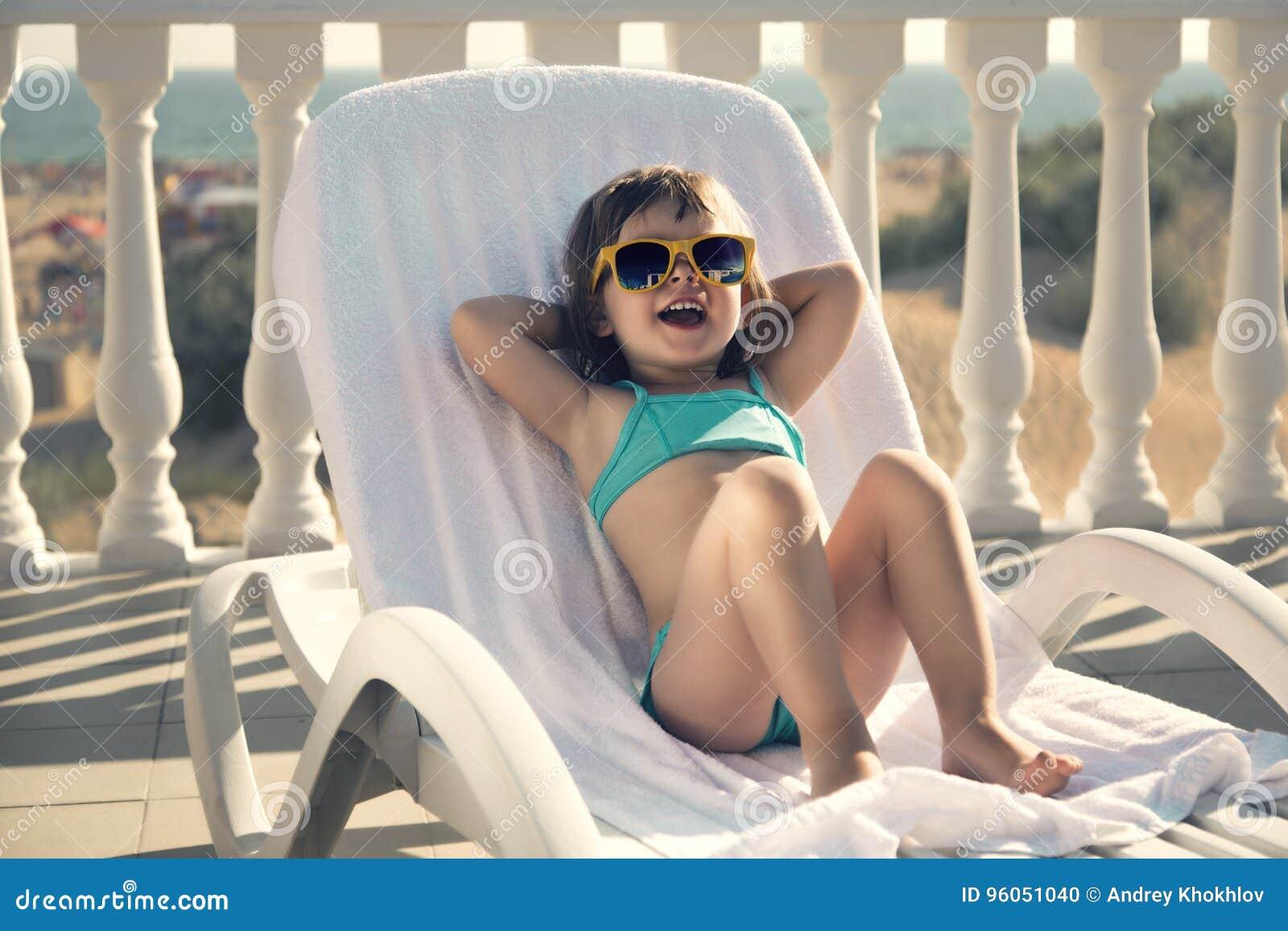 A menina engraçada toma sol em um vadio do sol