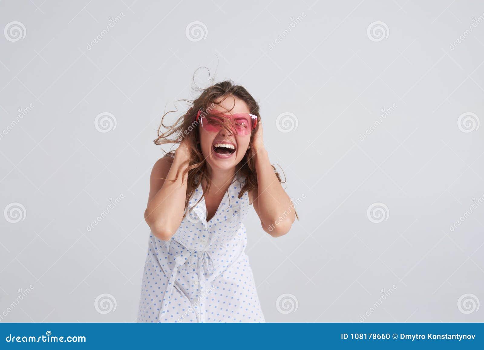 Menina entusiasmado nos óculos de sol cor-de-rosa que vão loucos