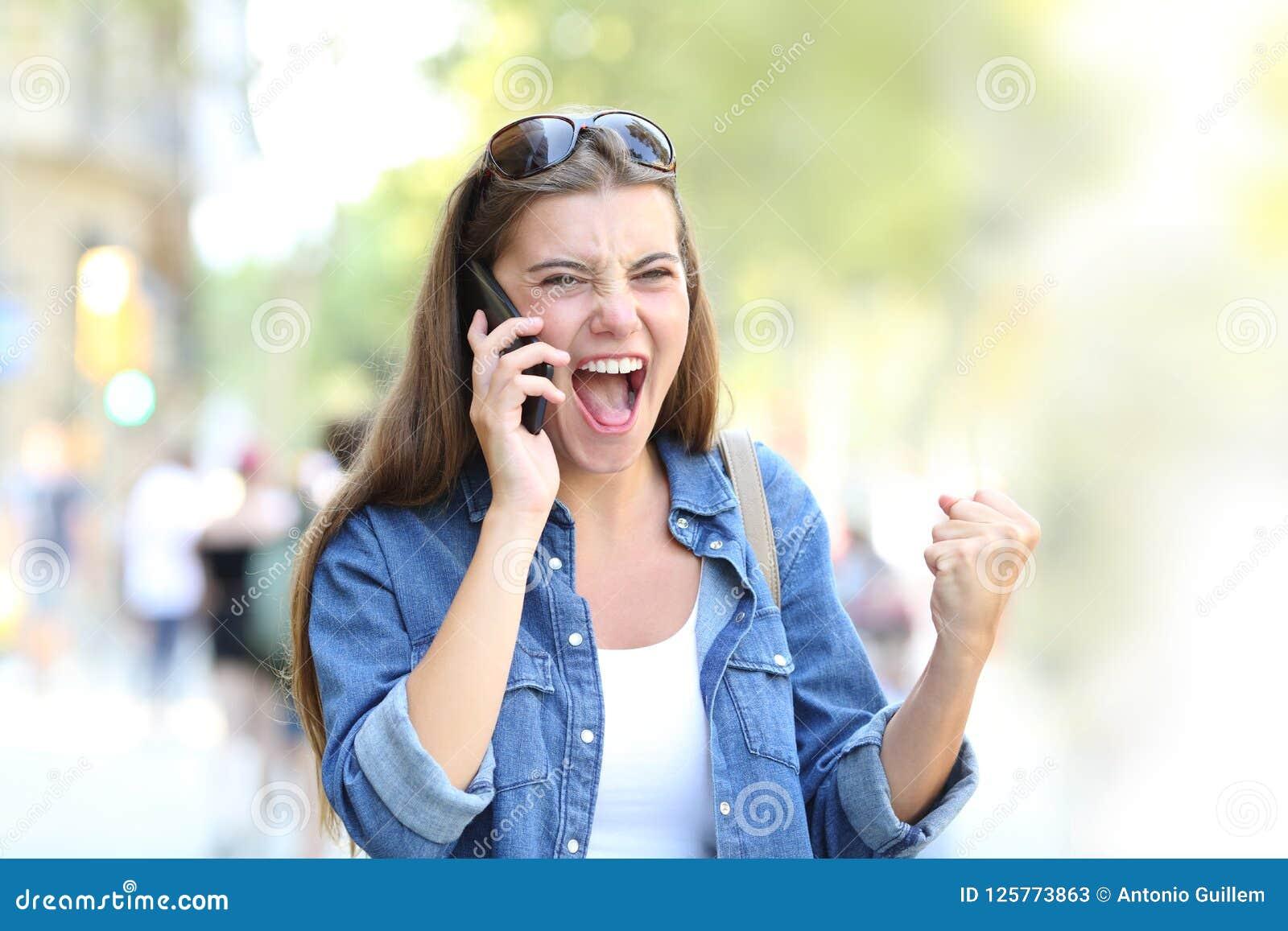 Menina entusiasmado que tem uma conversa telefônica na rua
