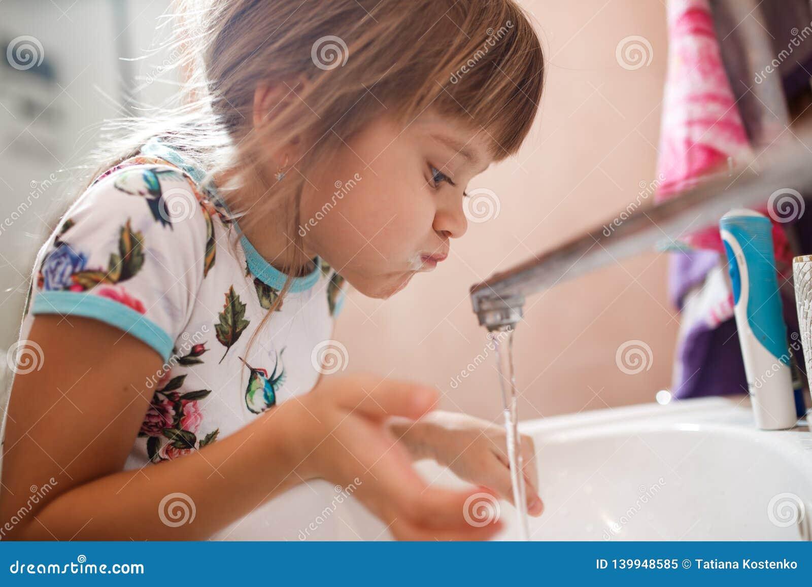 A menina enxágua sua boca com água após ter escovado seus dentes no banheiro