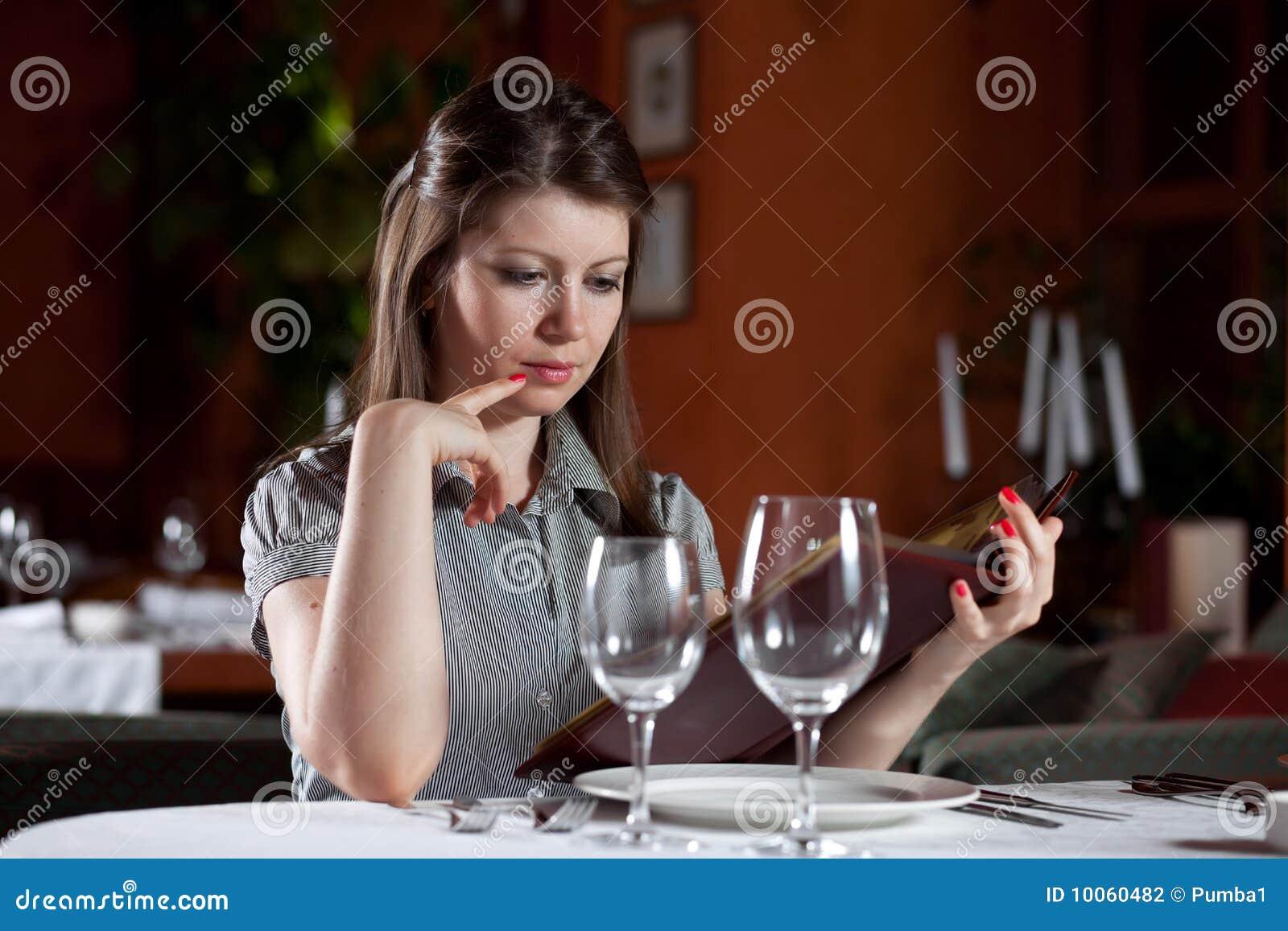 A menina escolhe a refeição no restaurante