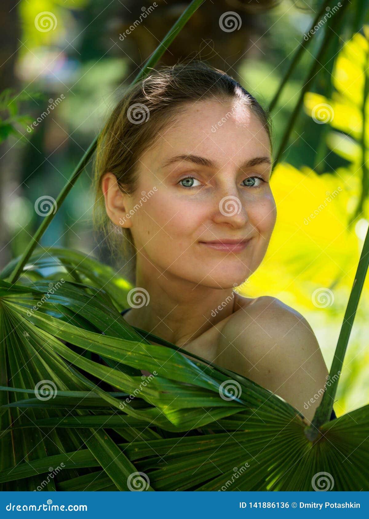 A menina escondeu atrás das folhas de palmeira