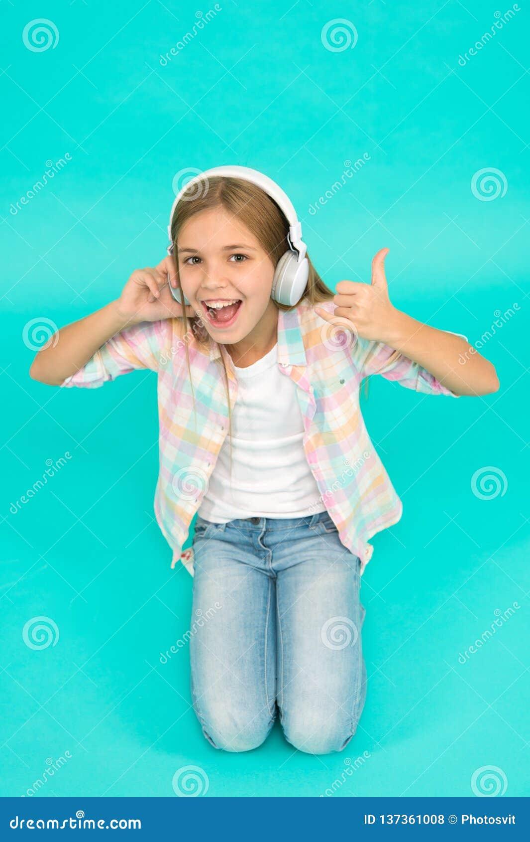 A menina escuta fones de ouvido da música Aprecie a trilha da faixa favorita A criança da menina escuta fones de ouvido modernos