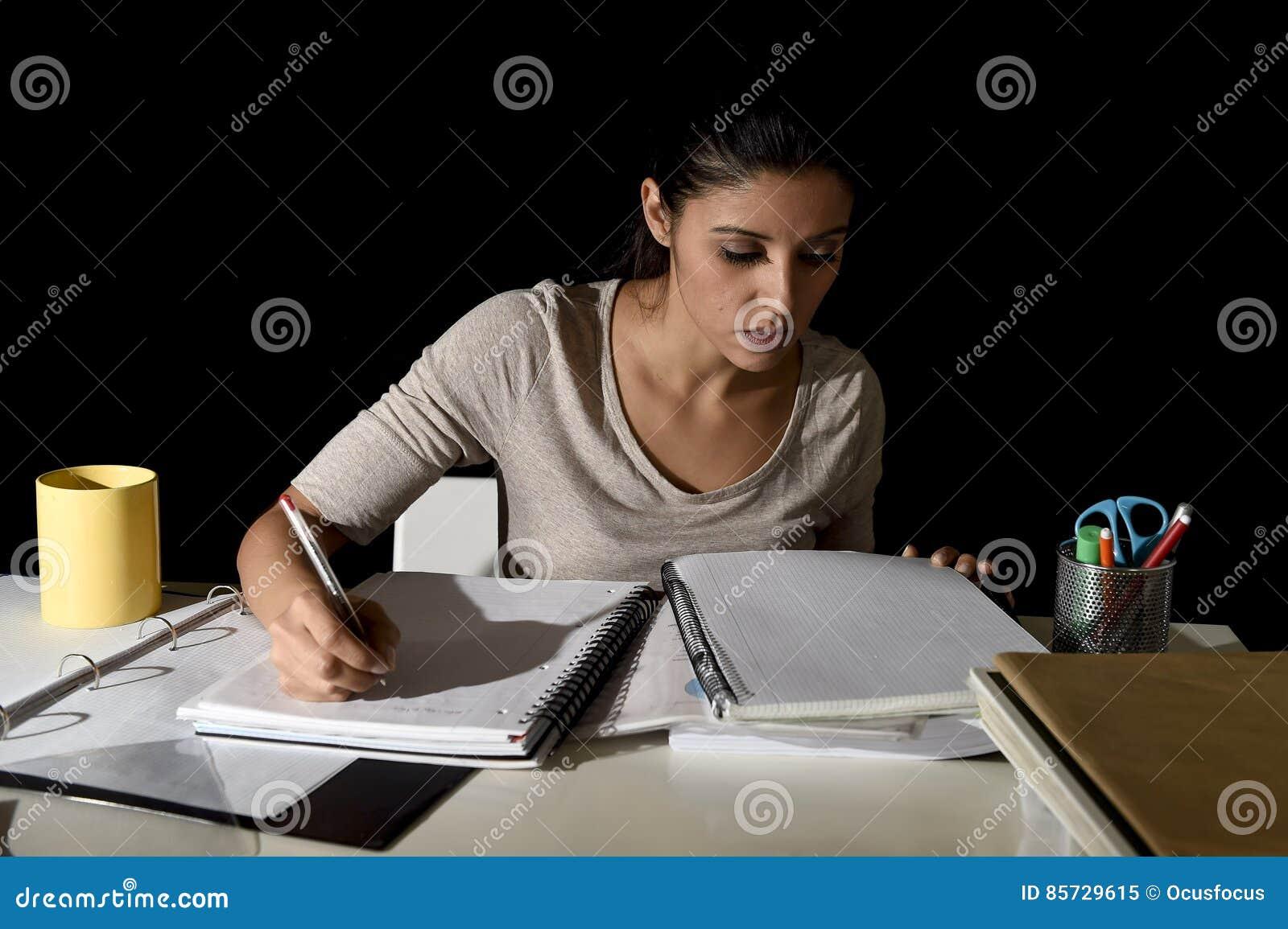Menina espanhola bonita ocupada nova que estuda em casa o exame de preparação de vista tardio concentrado