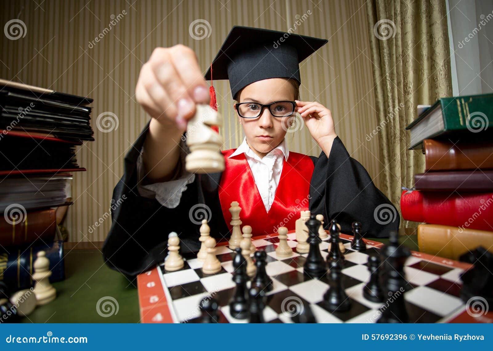 Menina esperta no tampão da graduação que faz o movimento na xadrez com cavalo