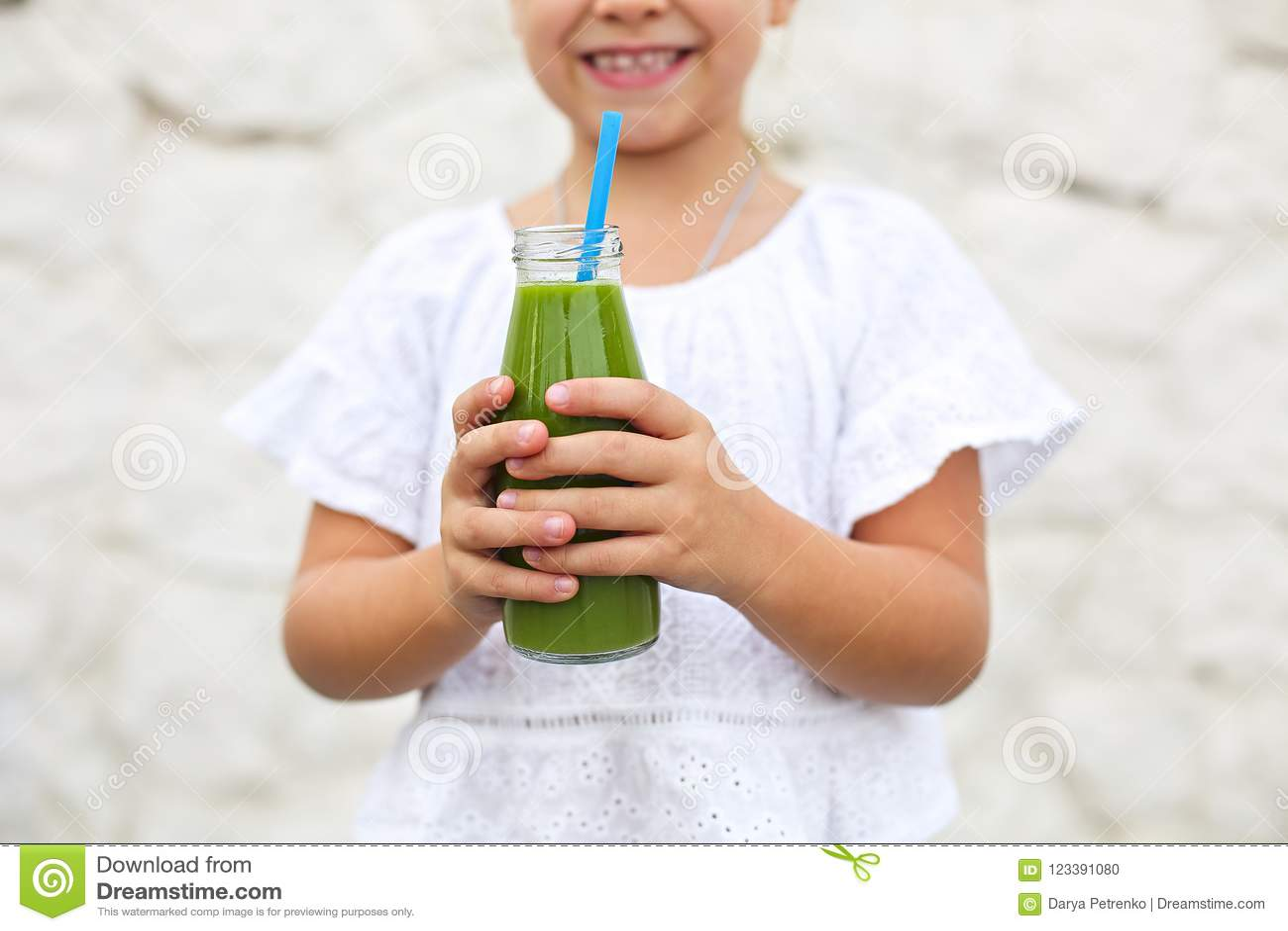 A menina está bebendo o suco fresco verde usando a palha fora