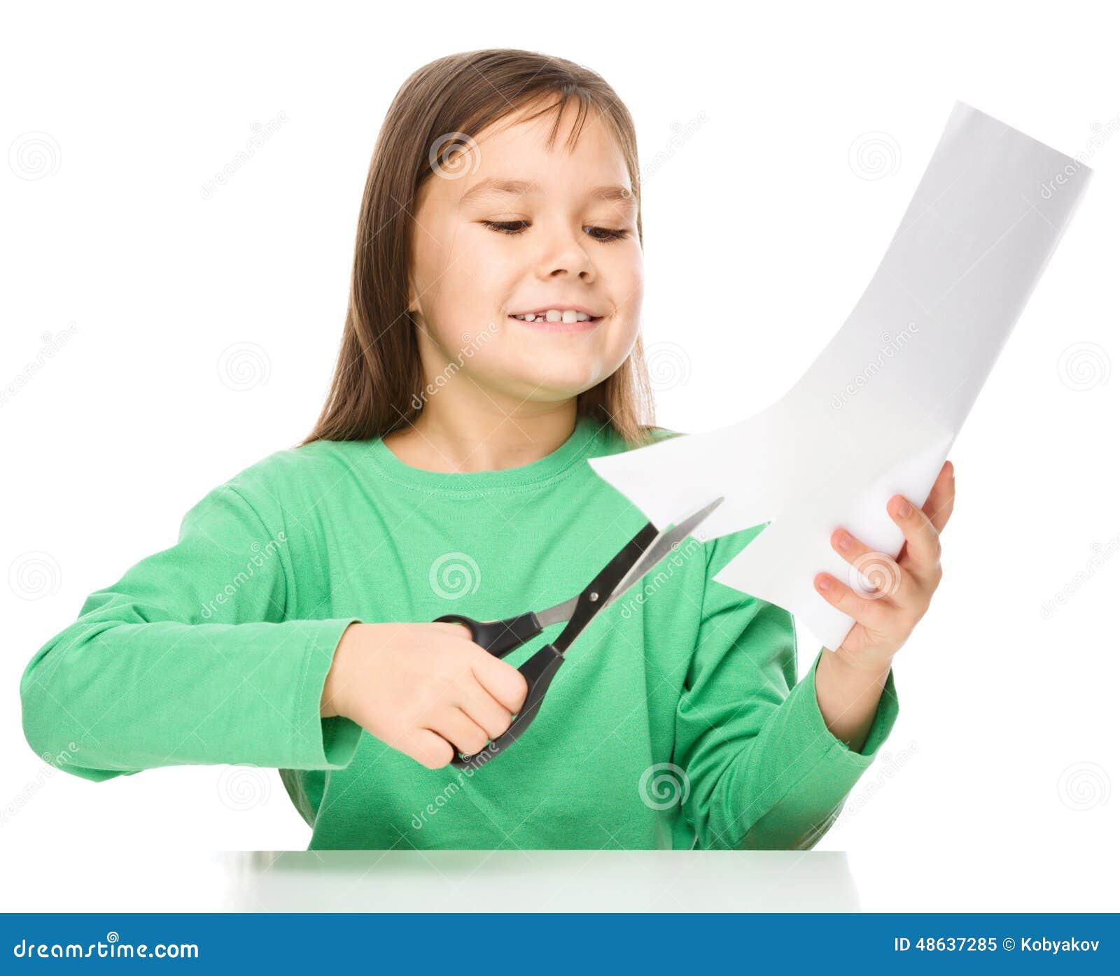 A menina está cortando o papel usando tesouras
