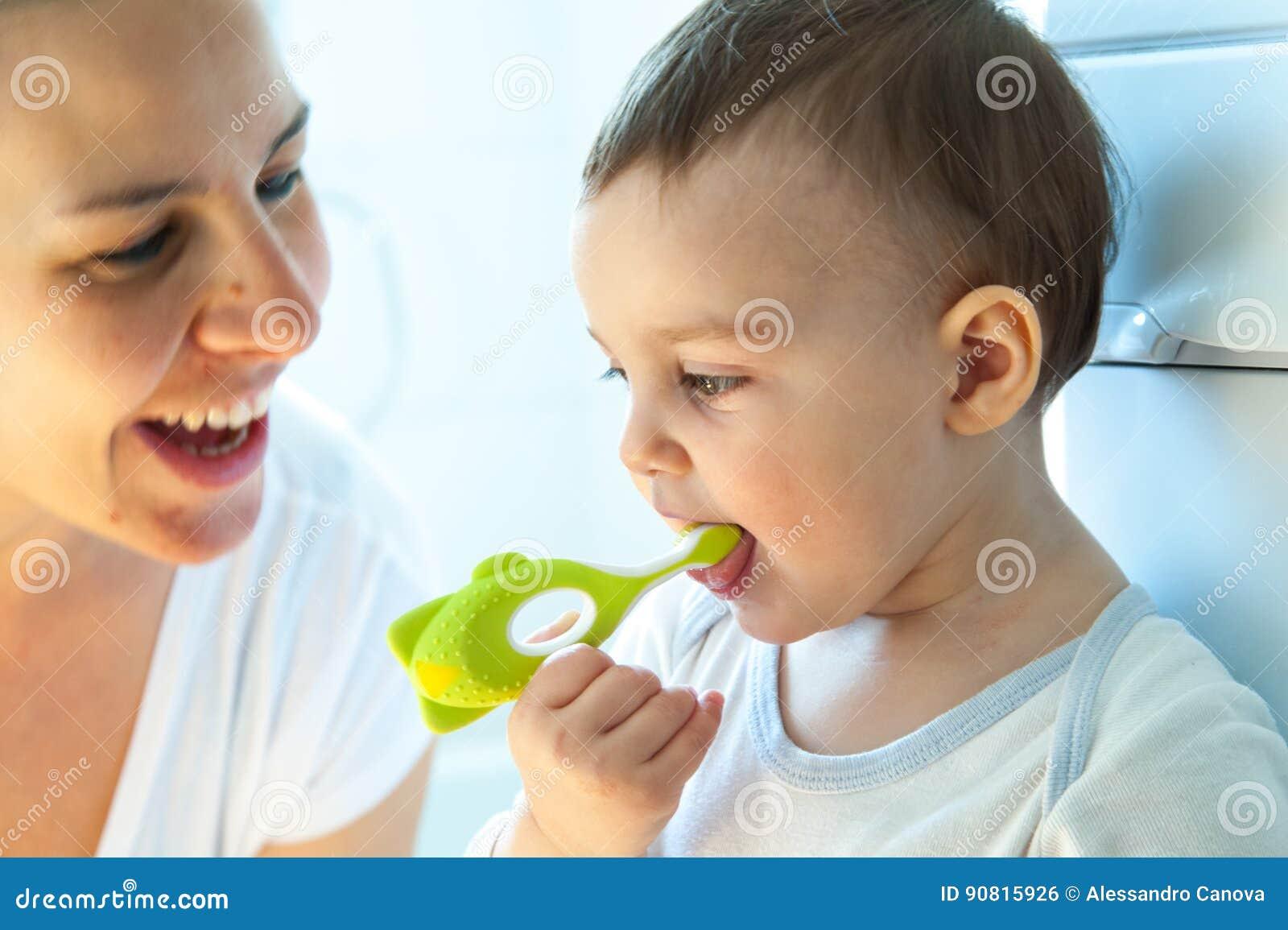 A menina está escovando os dentes com sua escova de dentes