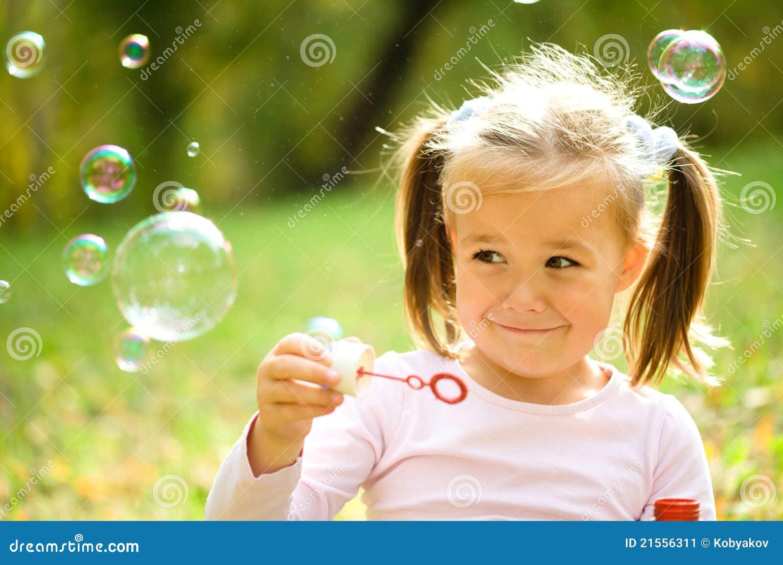 A menina está fundindo bolhas de sabão