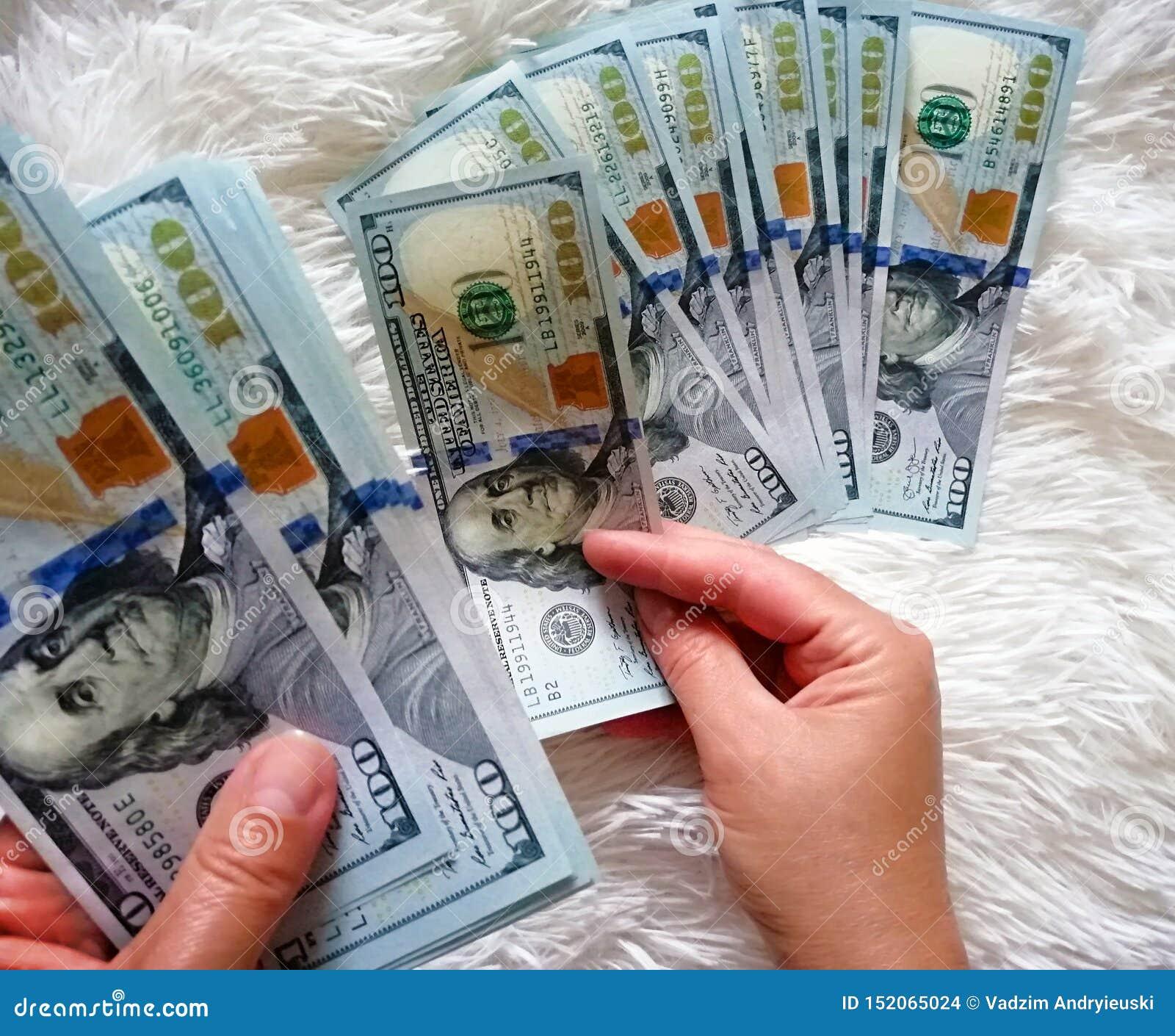 A menina está guardando o dinheiro em suas mãos Cem dólares de dinheiro