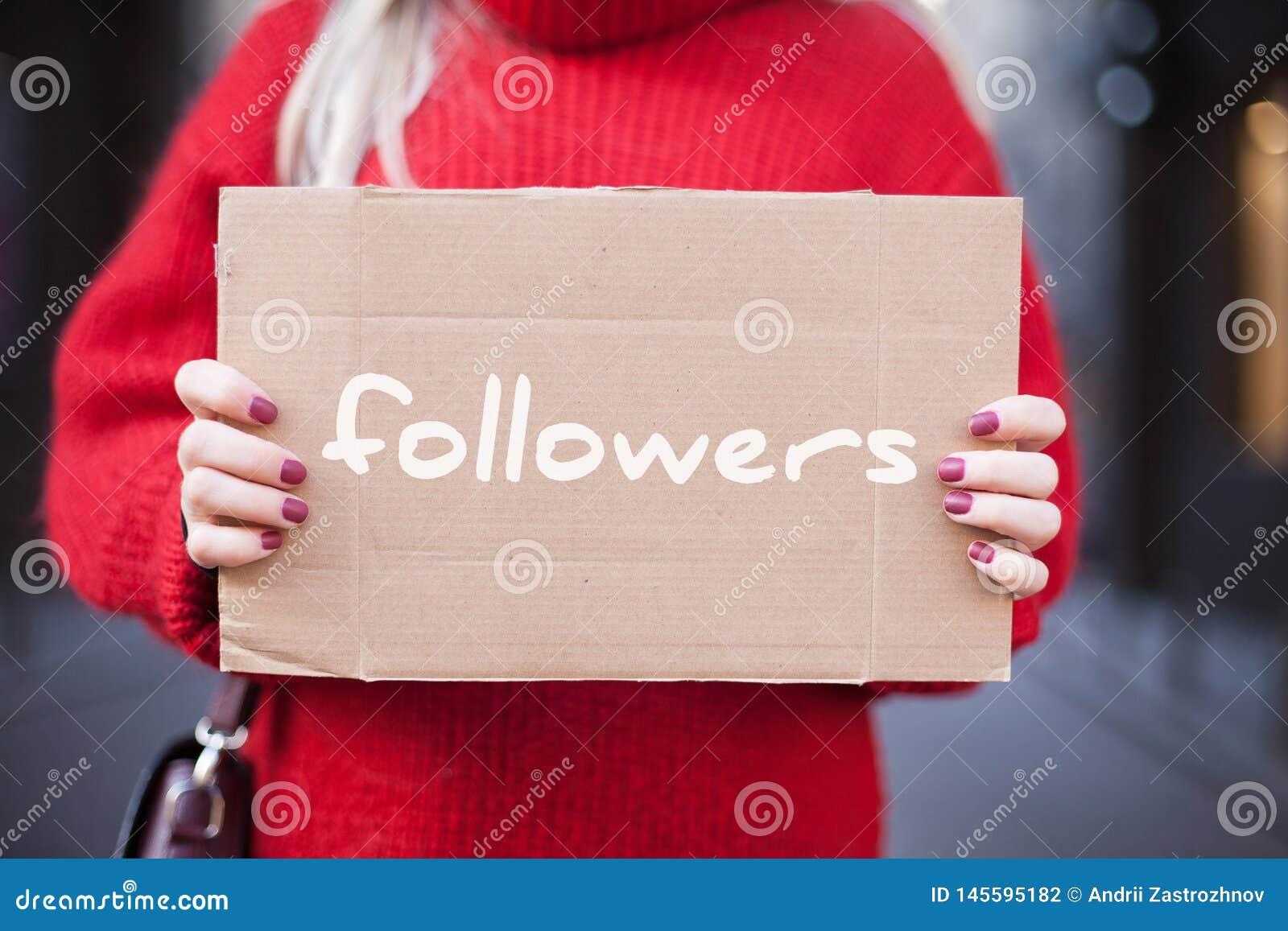 A menina está guardando uma tabuleta do cartão em suas mãos com os seguidores da inscrição '