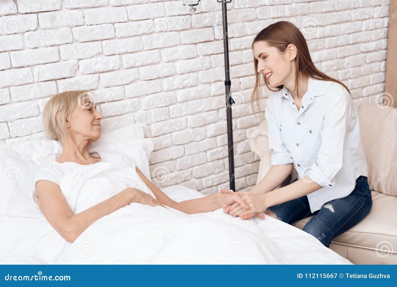 A menina está importando-se com a mulher idosa em casa Estão guardando as mãos