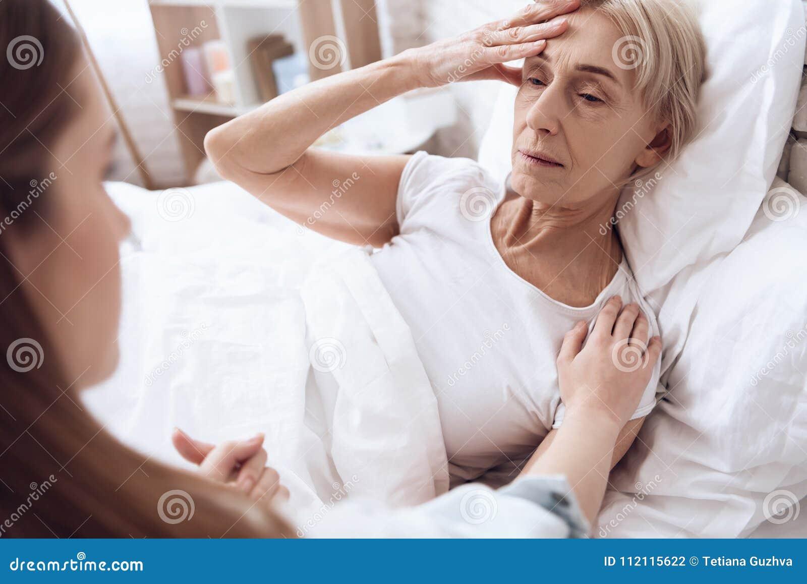A menina está importando-se com a mulher idosa em casa Estão guardando as mãos A mulher está sentindo má