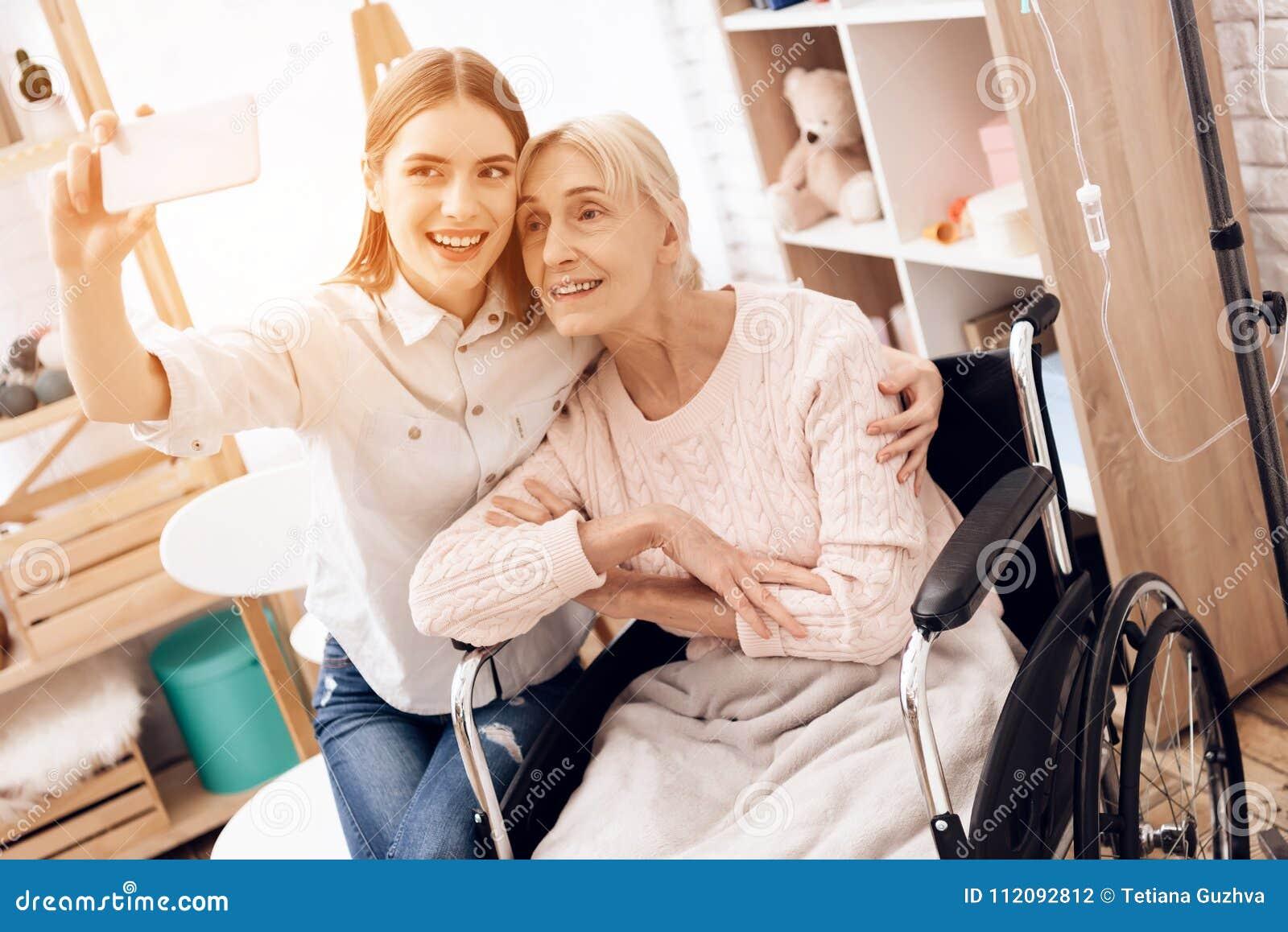 A menina está importando-se com a mulher idosa em casa Estão tomando o selfie no telefone