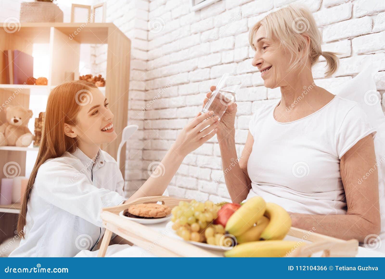 A menina está importando-se com a mulher idosa em casa A menina traz o café da manhã na bandeja A mulher é água potável