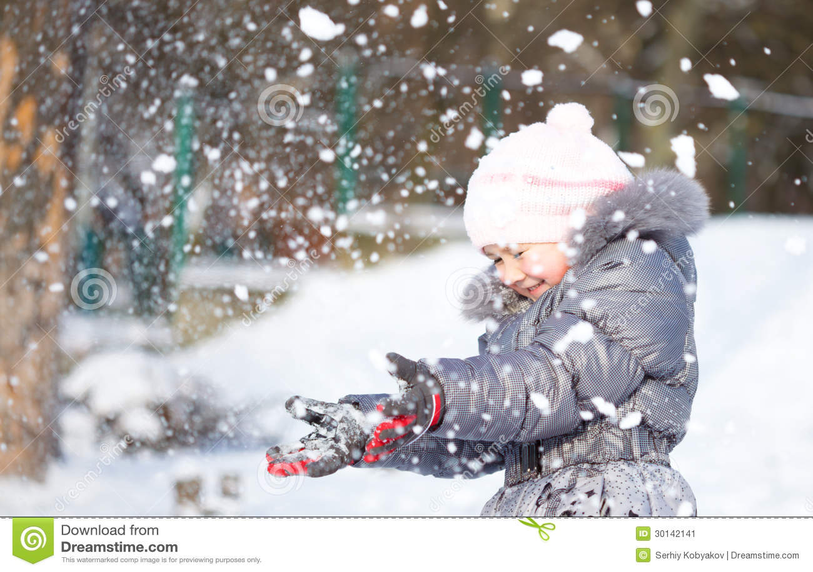 A menina está jogando a neve