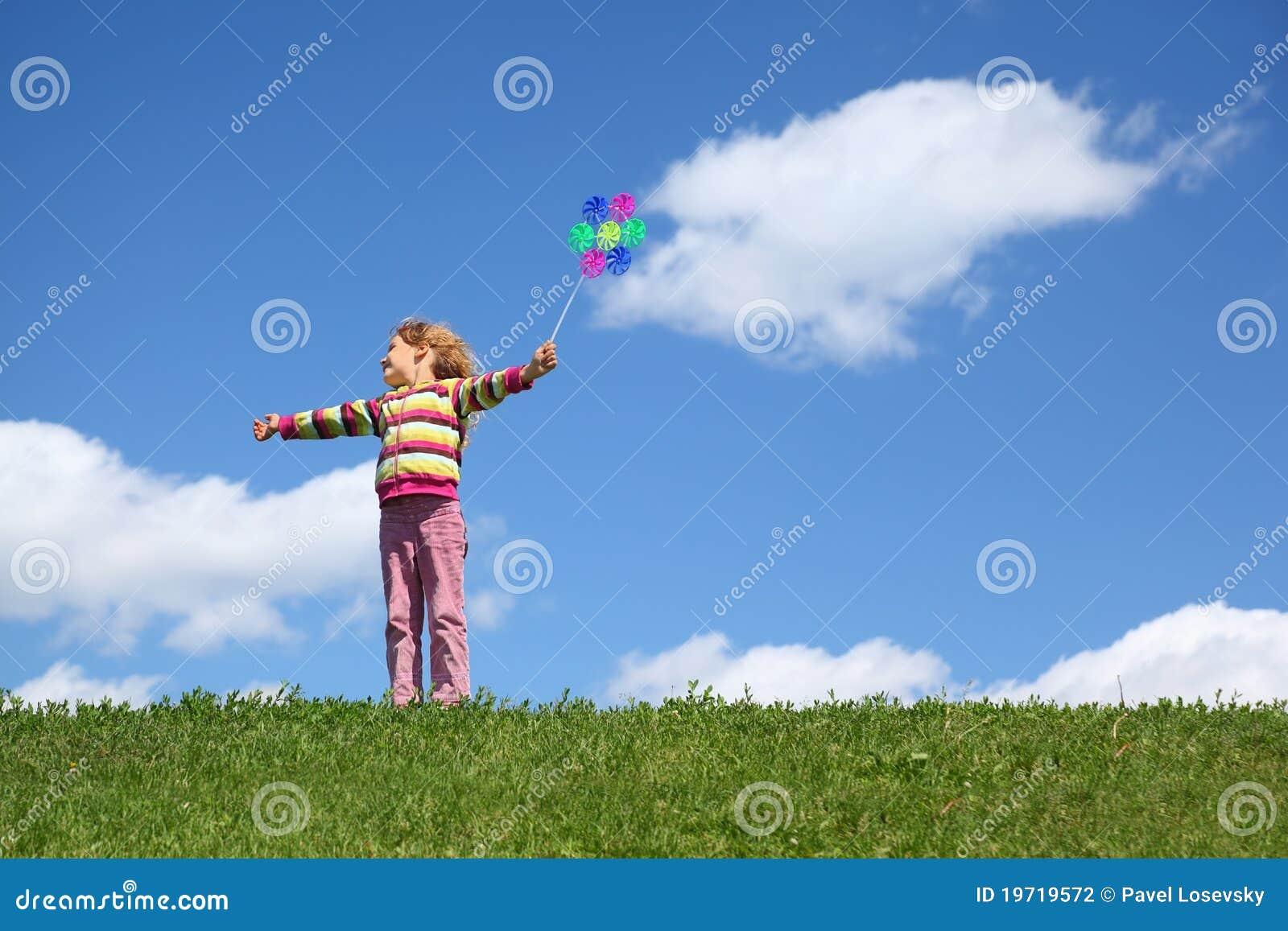 A menina está na grama e prende o moinho de vento